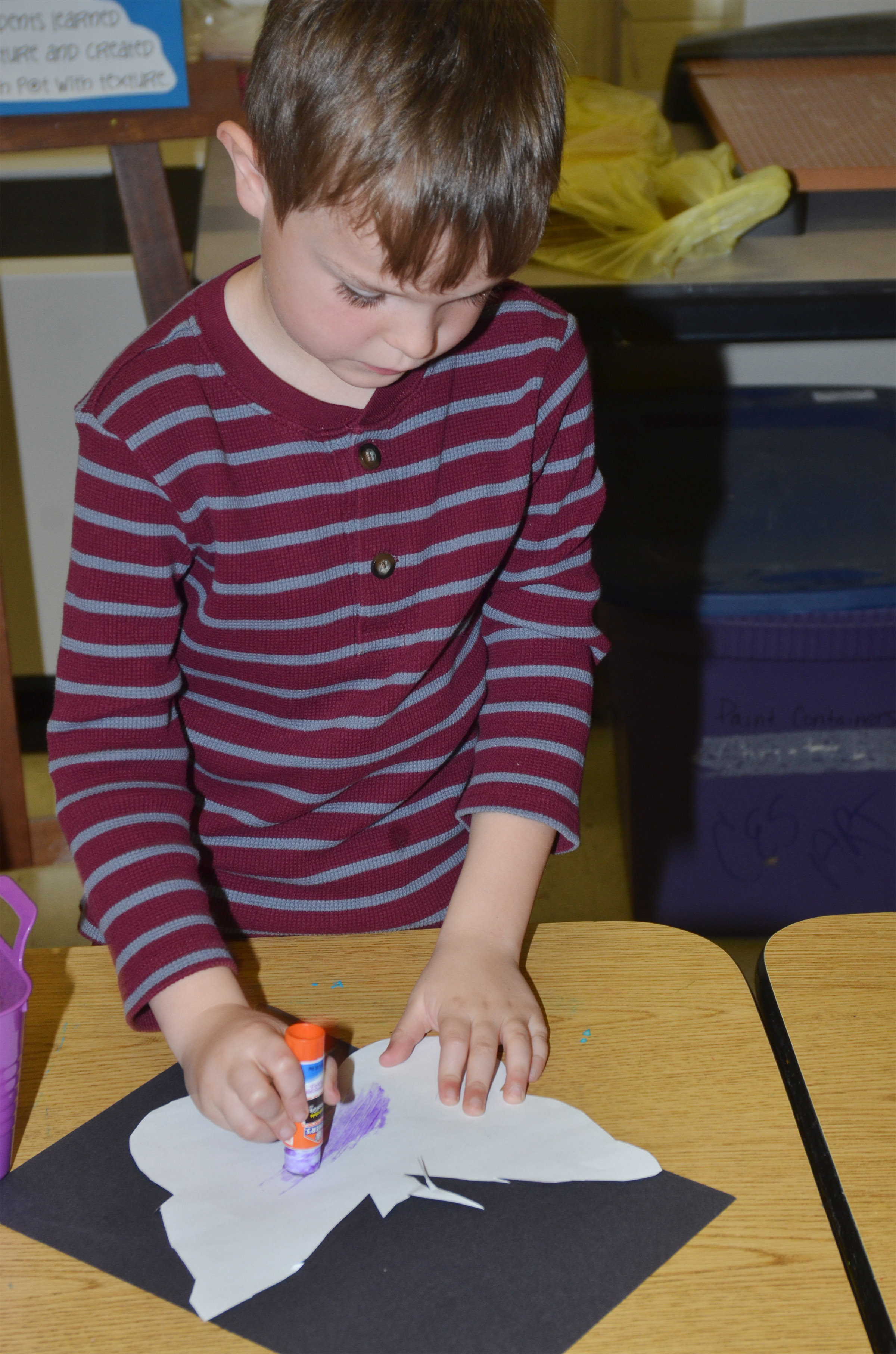 CES first-grader Karson Burchett creates emphasis as he glues his butterfly to black construction paper.