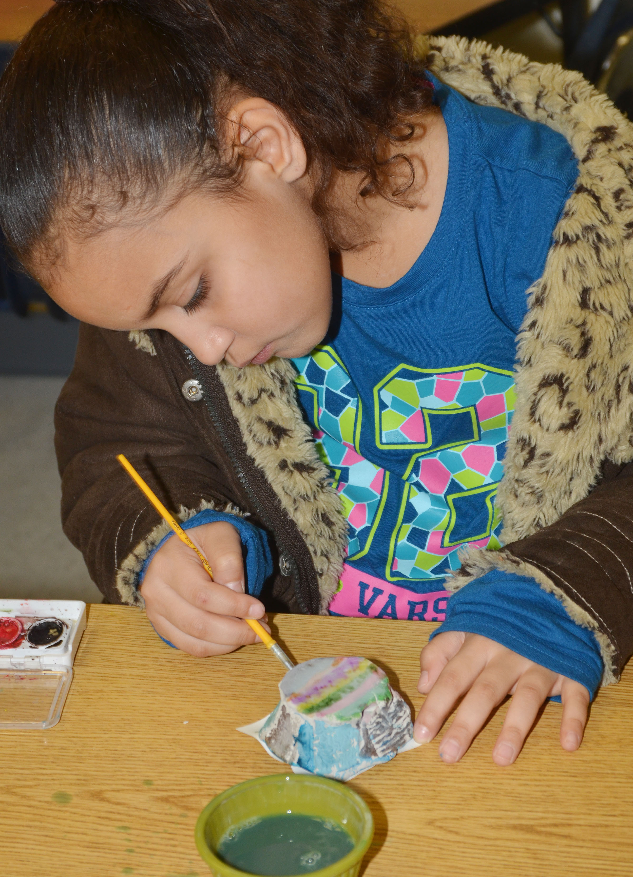 CES first-grader Maleigha Travis paints her pot.