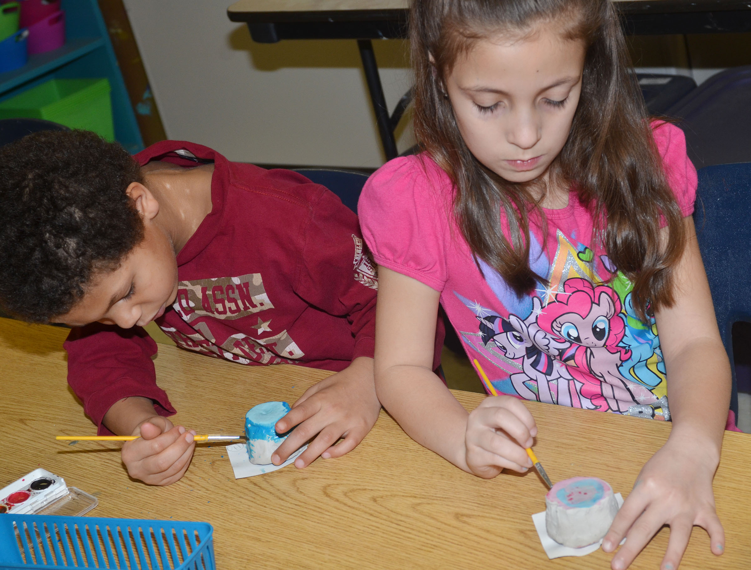 CES first-graders Tristen Williams, at left, and Lillian Martin paint their pots.
