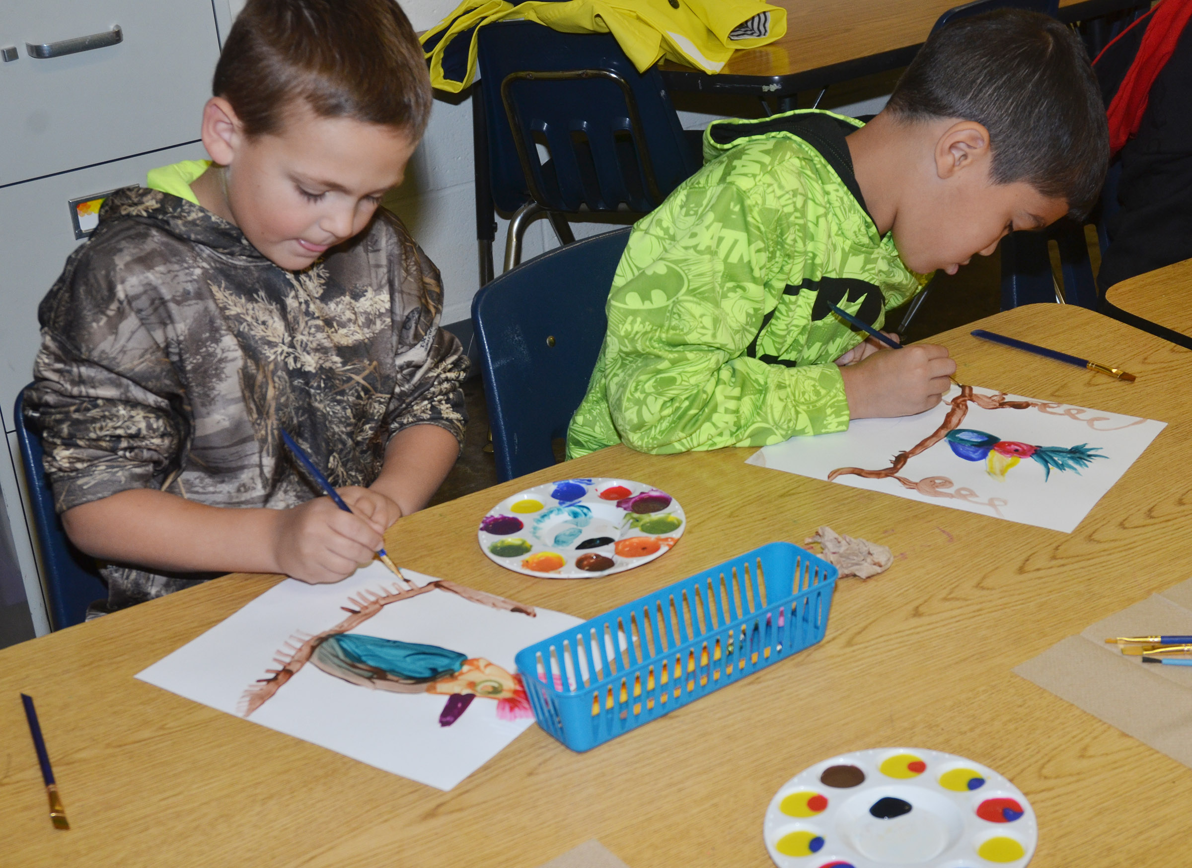 CES second-graders Brendan Martin, at left, and Xadrian Fugate paint.