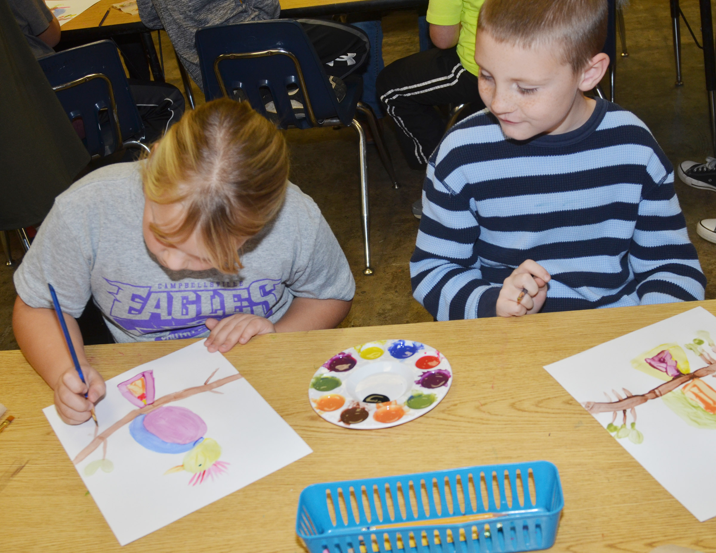 CES second-grader James Brunner watches as classmate Addysen England paints.