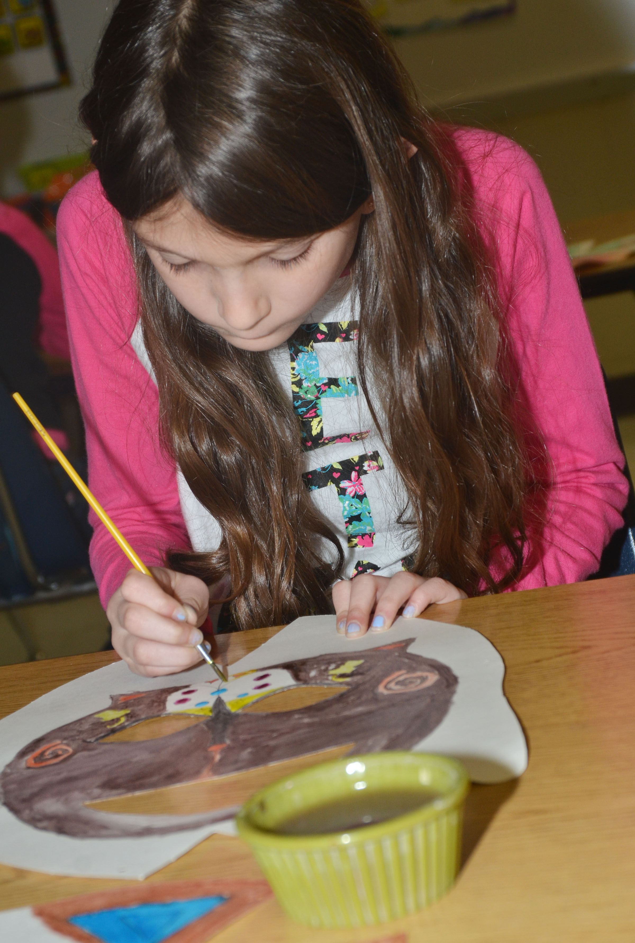 CES third-grader Madie Gebler paints her African mask.