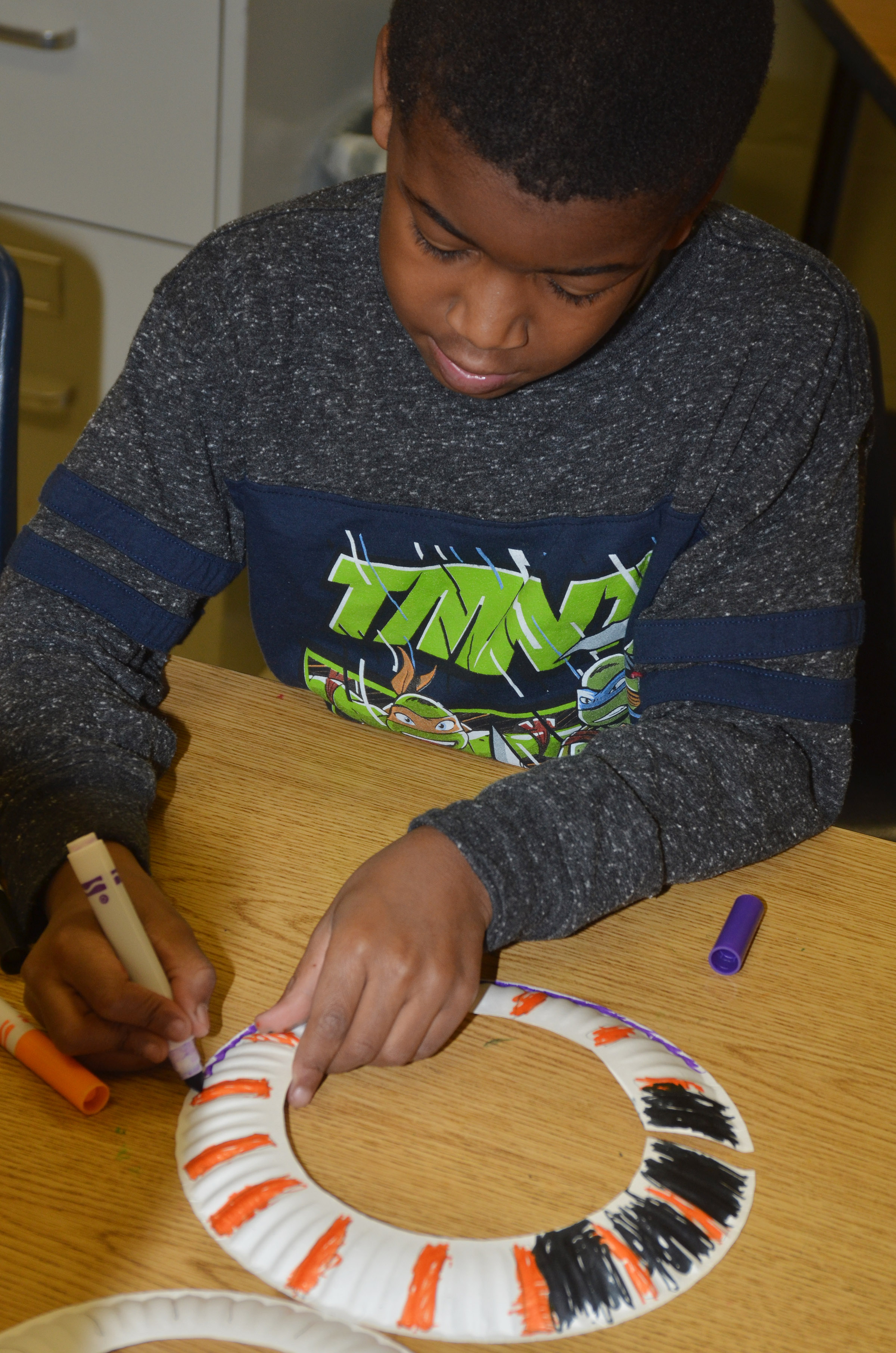 CES second-grader Kae'vin Spaulding draws designs on his African necklace.