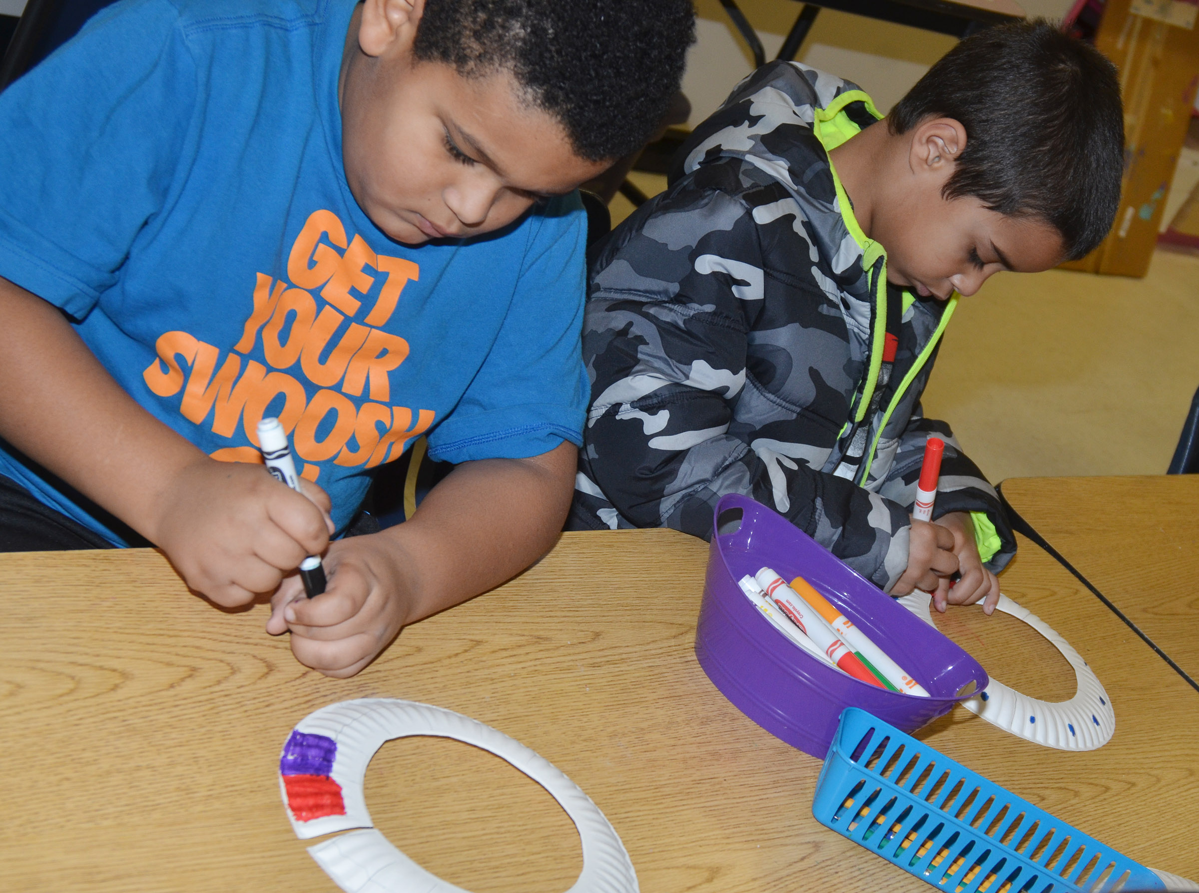 CES second-graders Jayden Moore, at left, and Keylan Strong color their African necklaces.