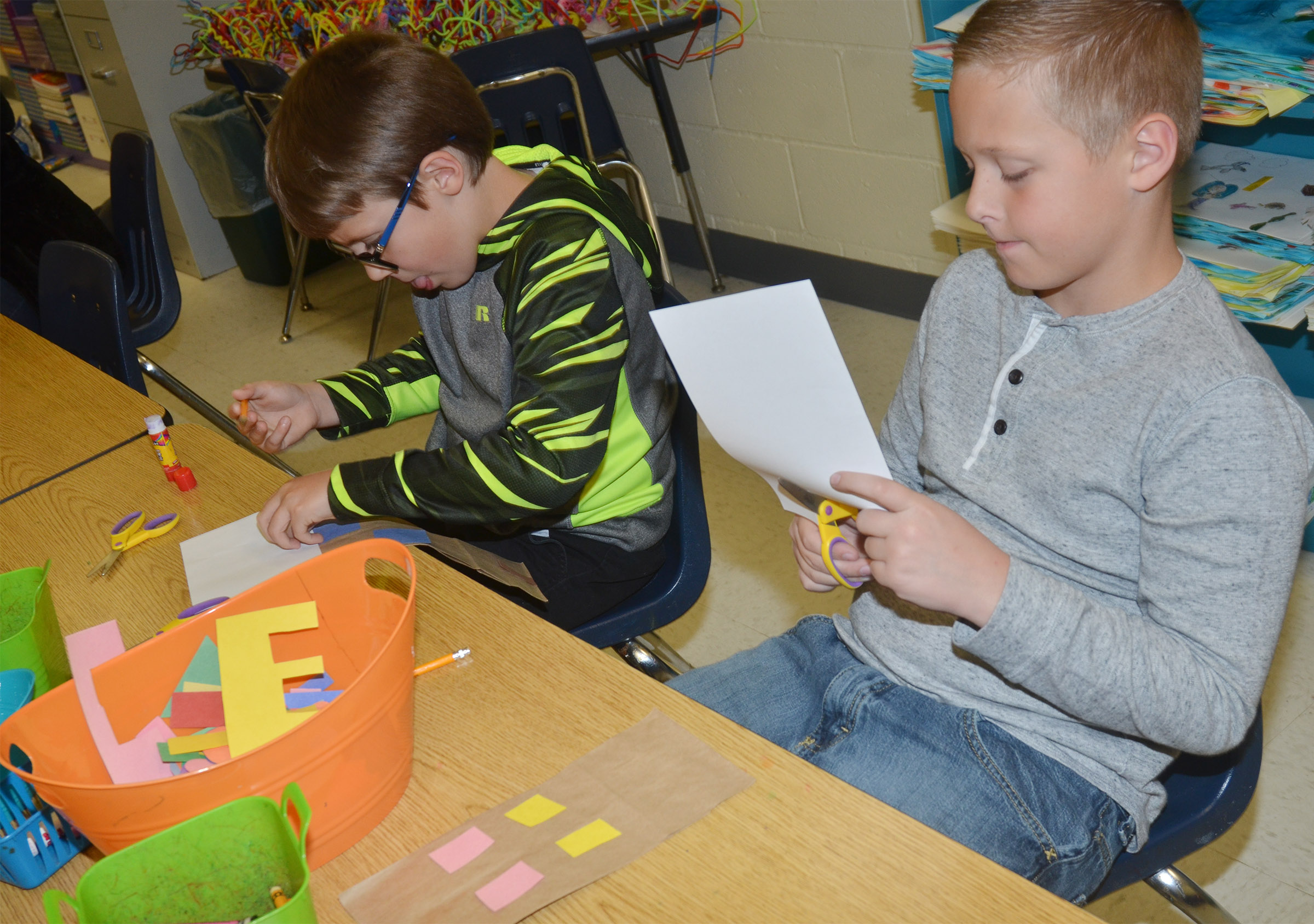 CES second-graders Dalton Shively, at left, and Evan Lockridge make their paper buildings.