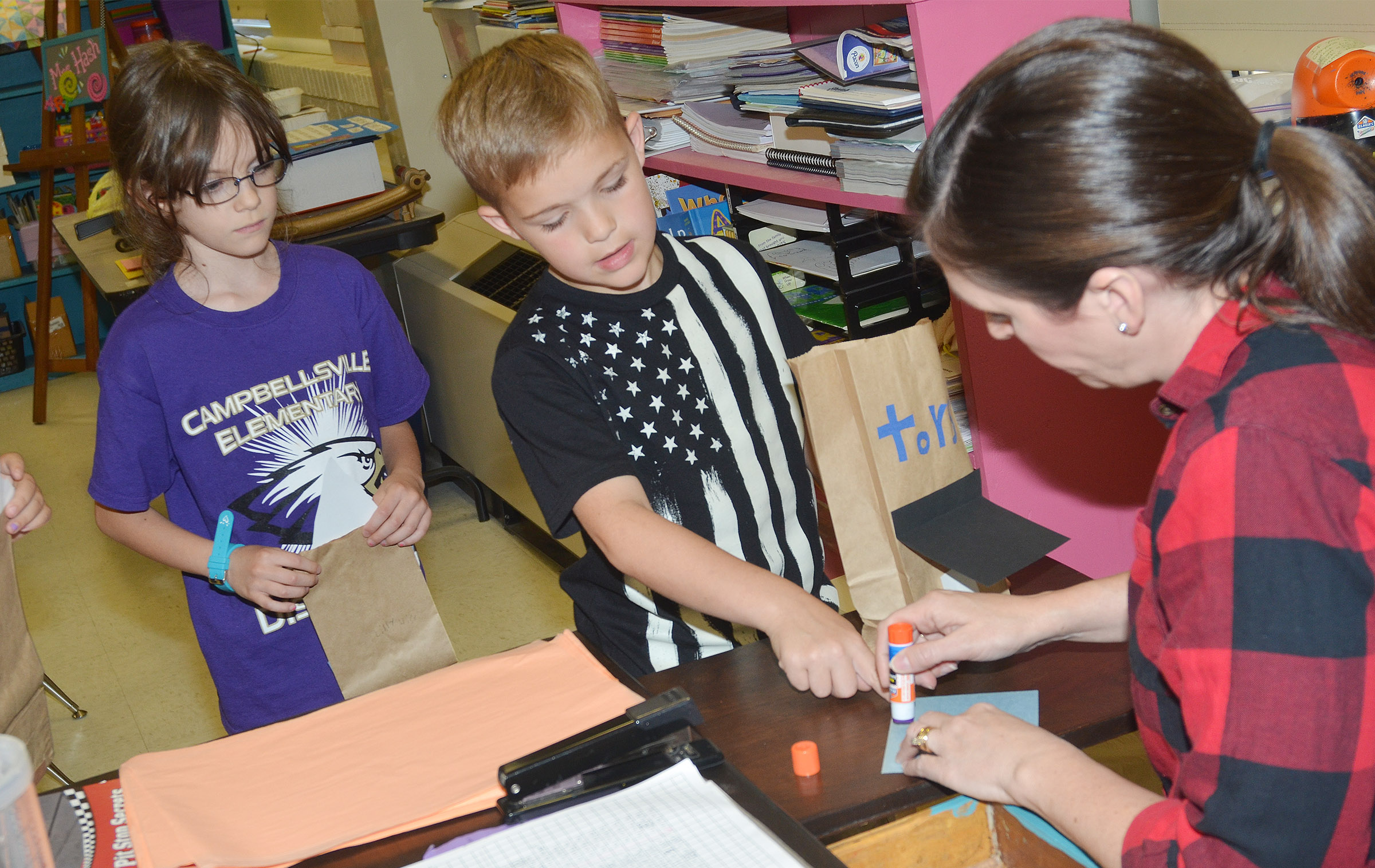 CES art teacher Adrienne Hash helps second-grader Kadin Coppage add tissue paper and a roof to his paper building.