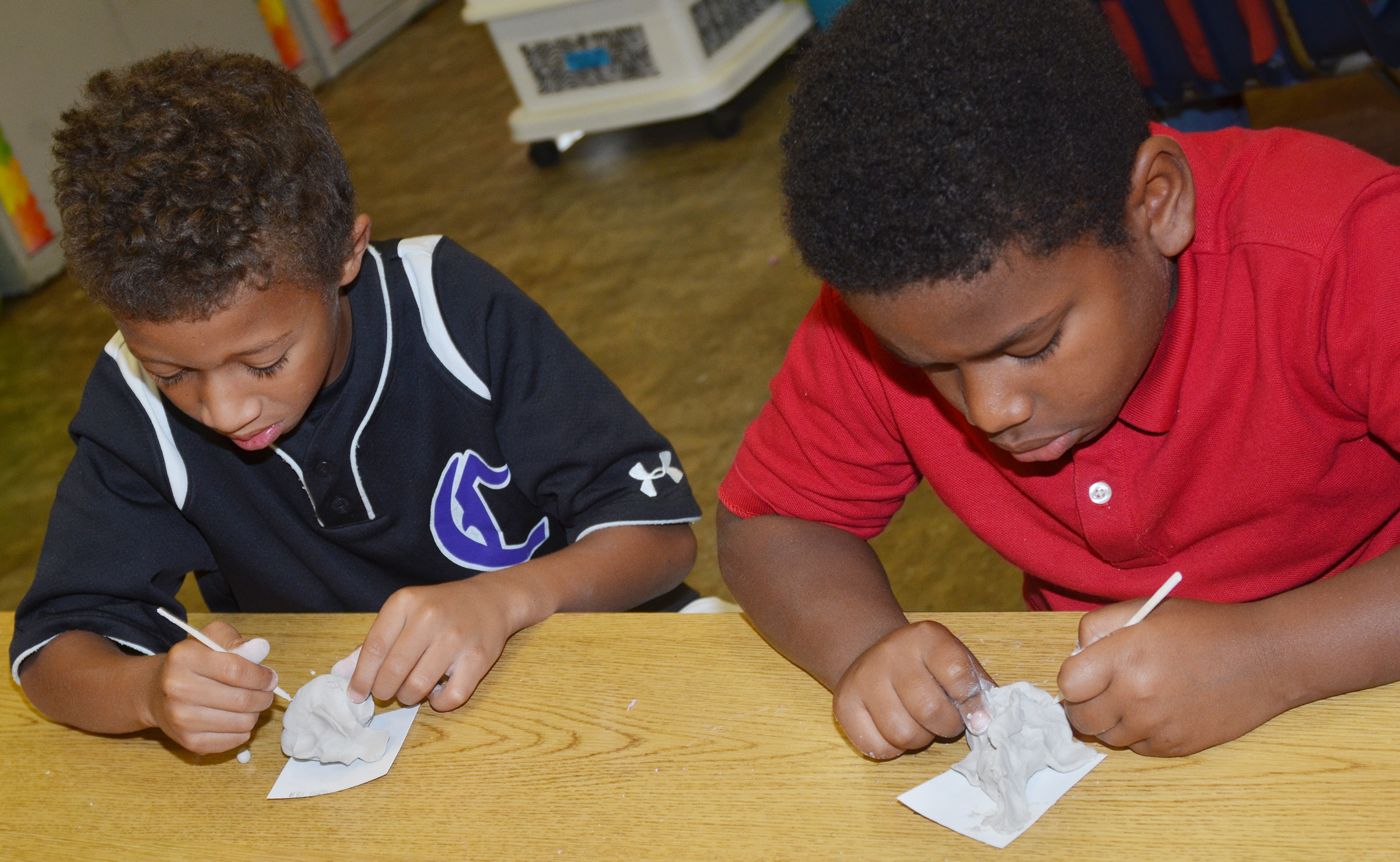CES third-graders Rajon Taylor, at left, and Elijah Spurling score their clay fish sculptures.
