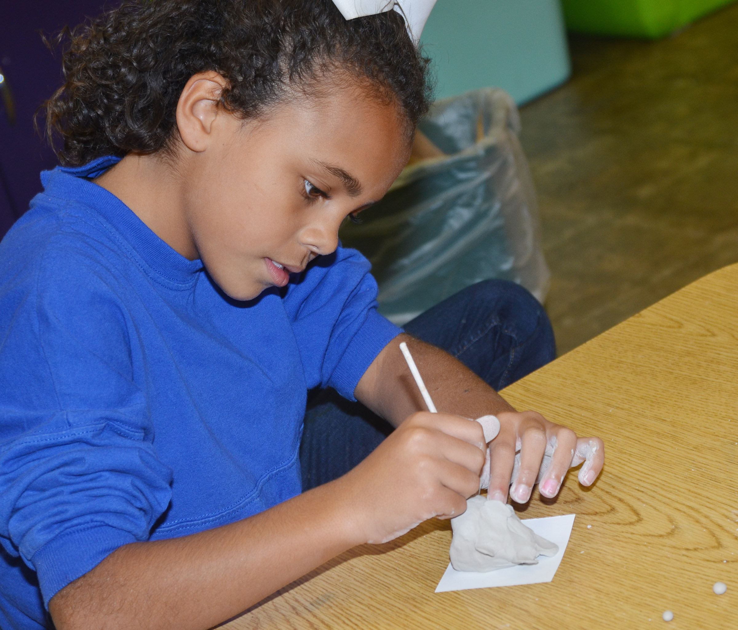 CES third-grader Braelyn Taylor scores her clay fish.