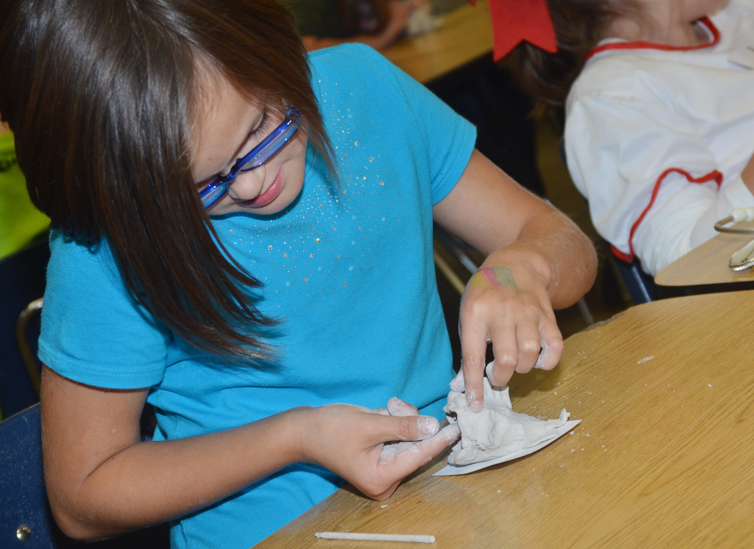 CES third-grader KayLee Lamer shapes the mouth on her clay fish.