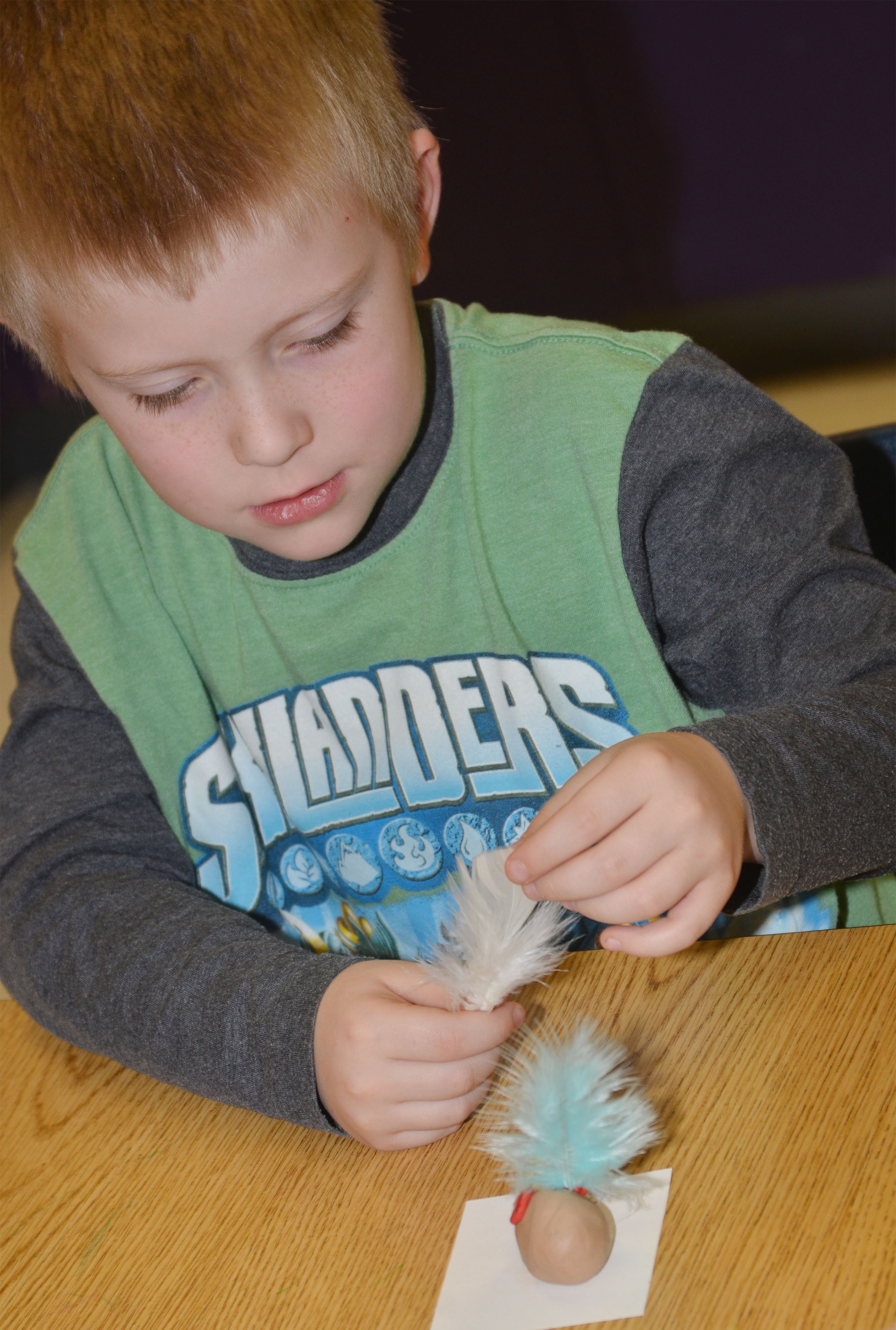 CES kindergartener Gage Henderson adds feathers to his owl.
