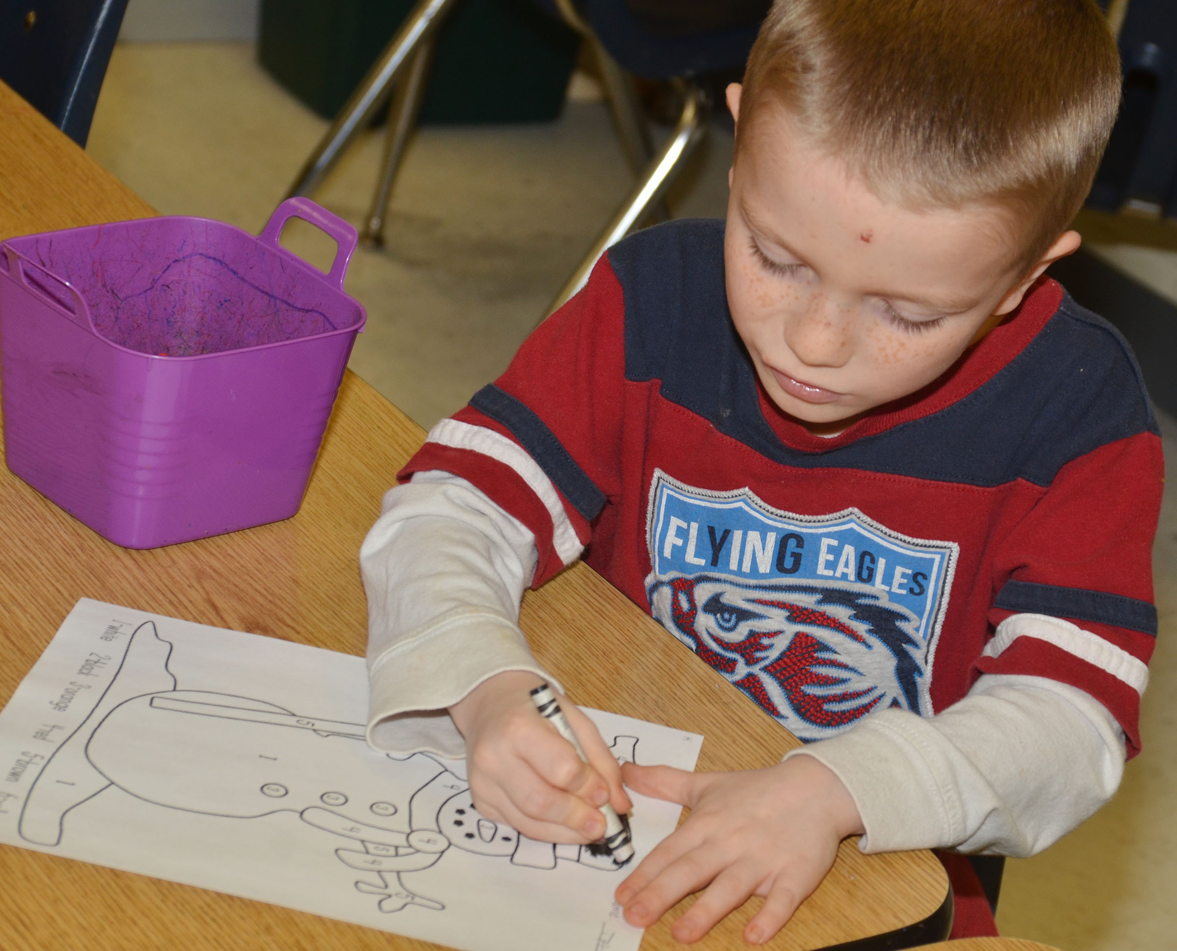 CES kindergartener Jason Eggers colors his snowman for the coloring contest.