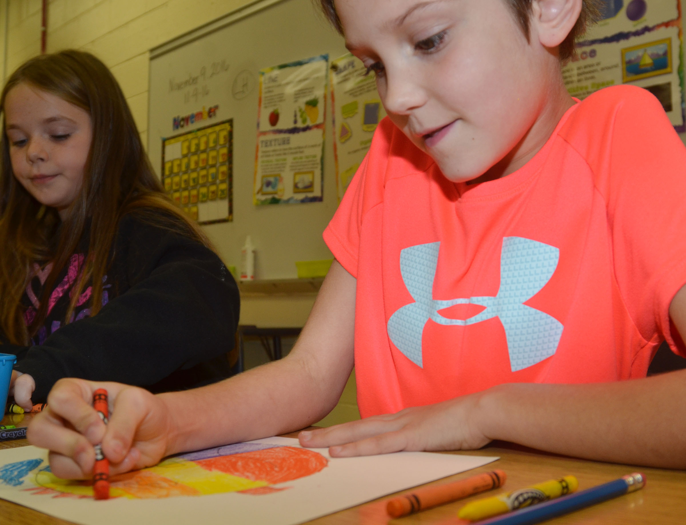 CES second-grader Baylee Pike colors her warm and cool color face.