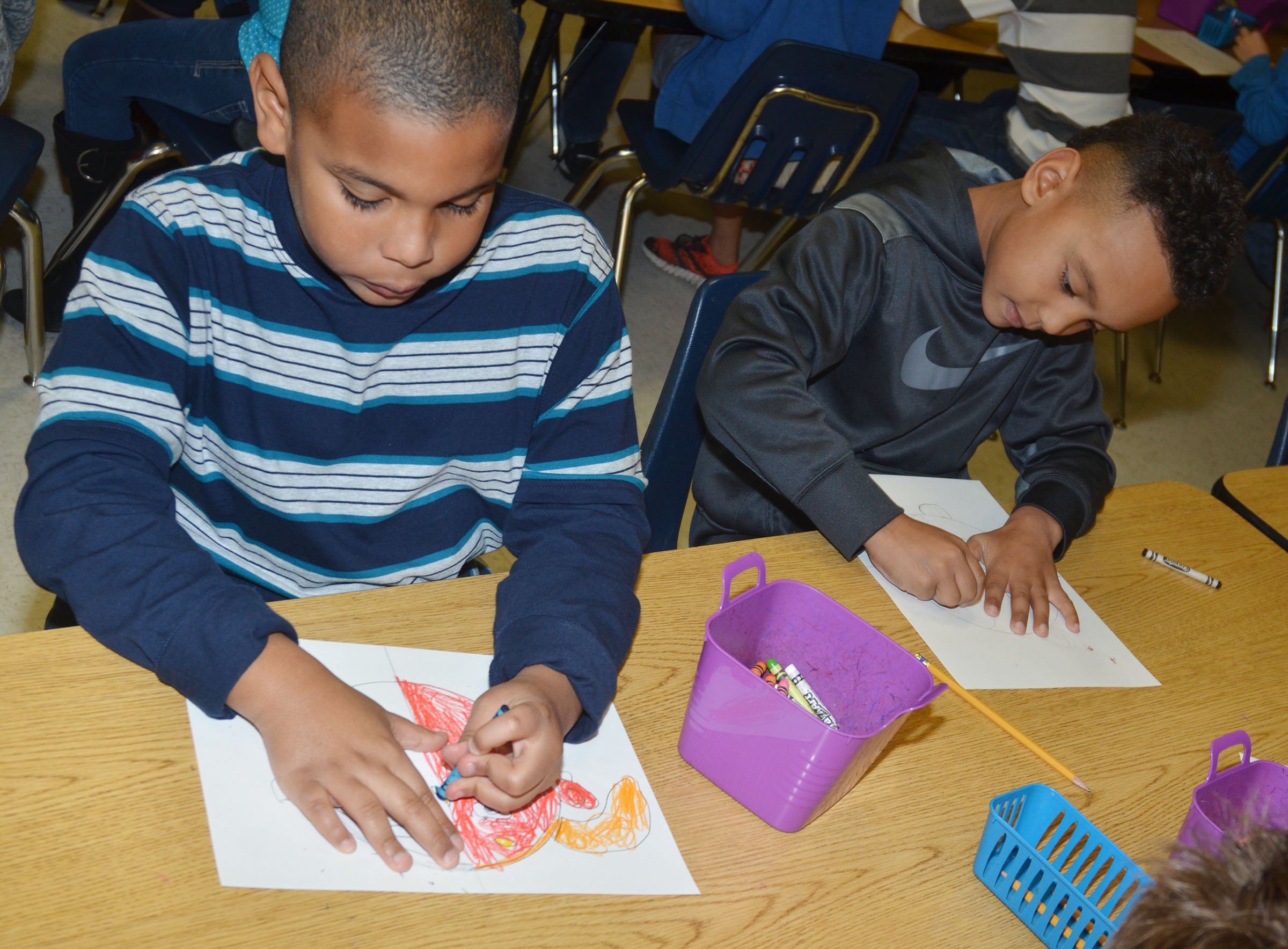 CES second-graders Zaemar Hoskins, at left, and Maddox Hawkins color their warm and cool color faces.