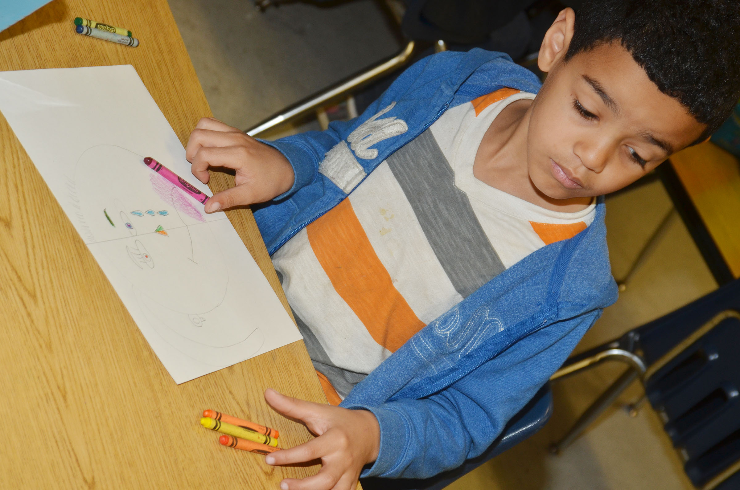 CES second-grader Leshawn Hamilton colors his warm and cool color face.