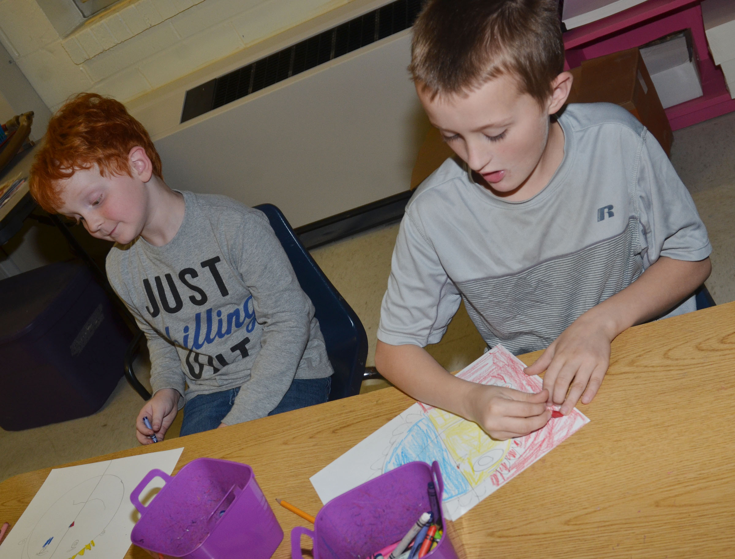CES second-graders Gavin Martin, at left, and Zachary Cox color their warm and cool color faces.
