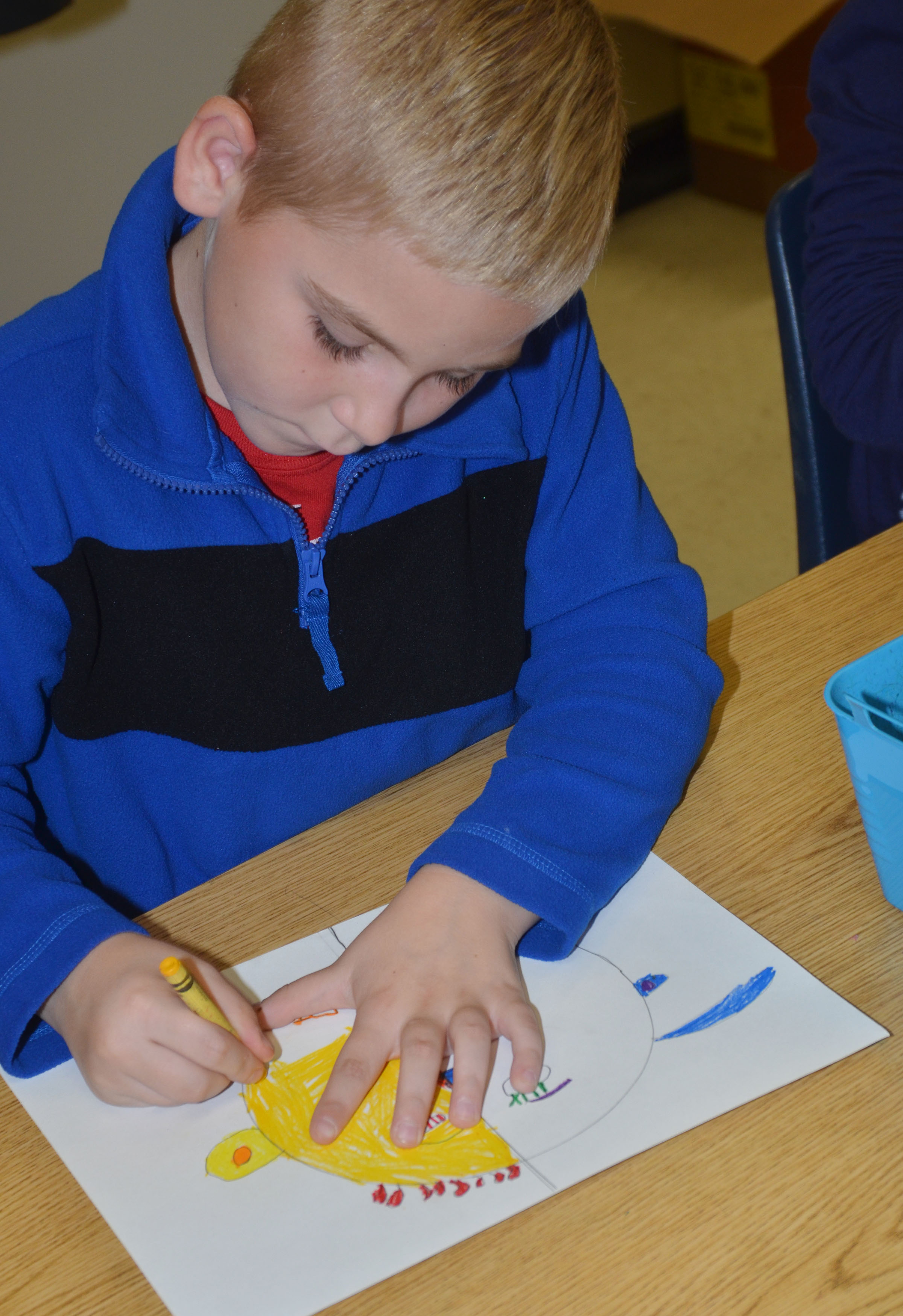 CES second-grader Joseph Greer colors his warm and cool color face.