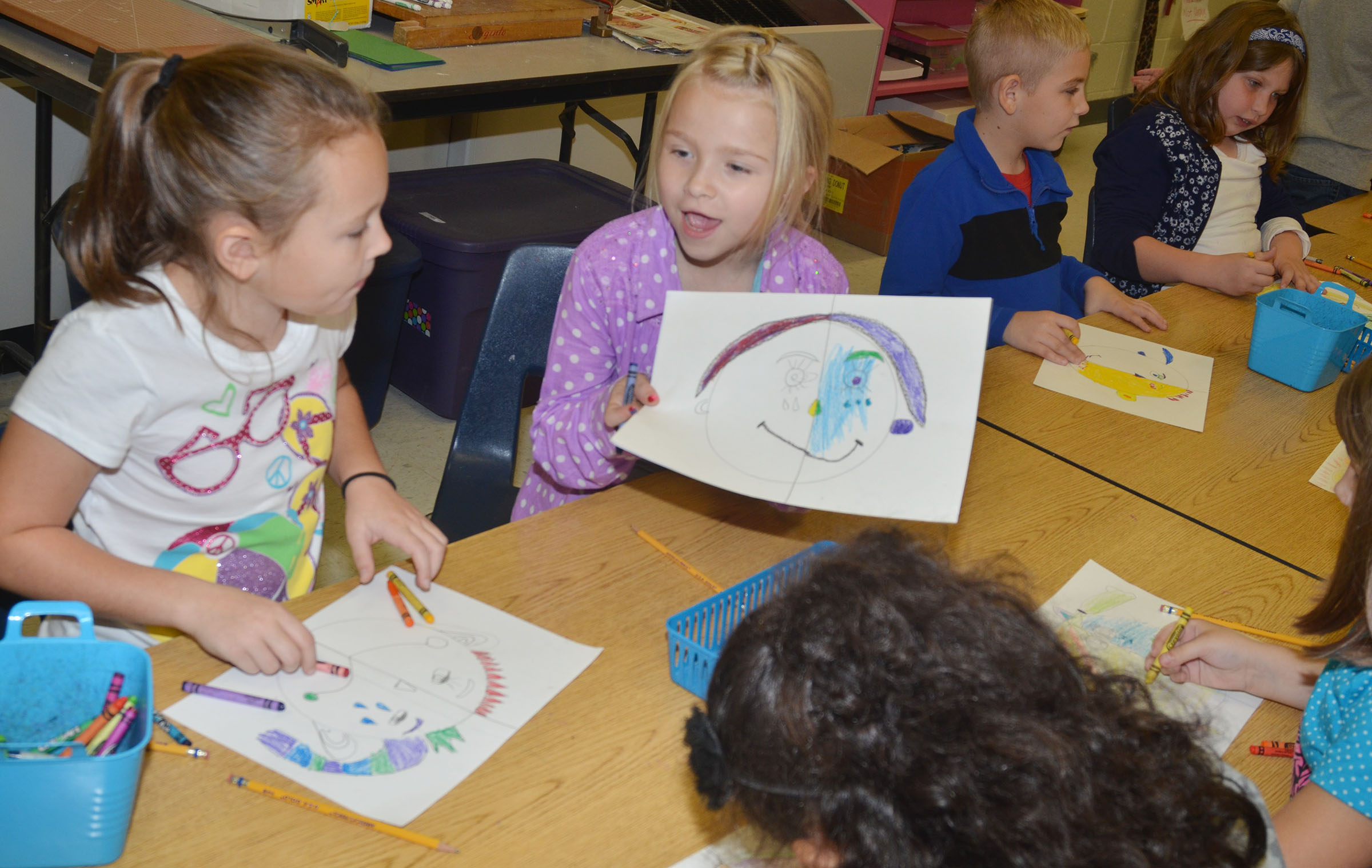 CES second-graders River McFarland, at left, and Lacy Covey talk about their warm and cool color faces.