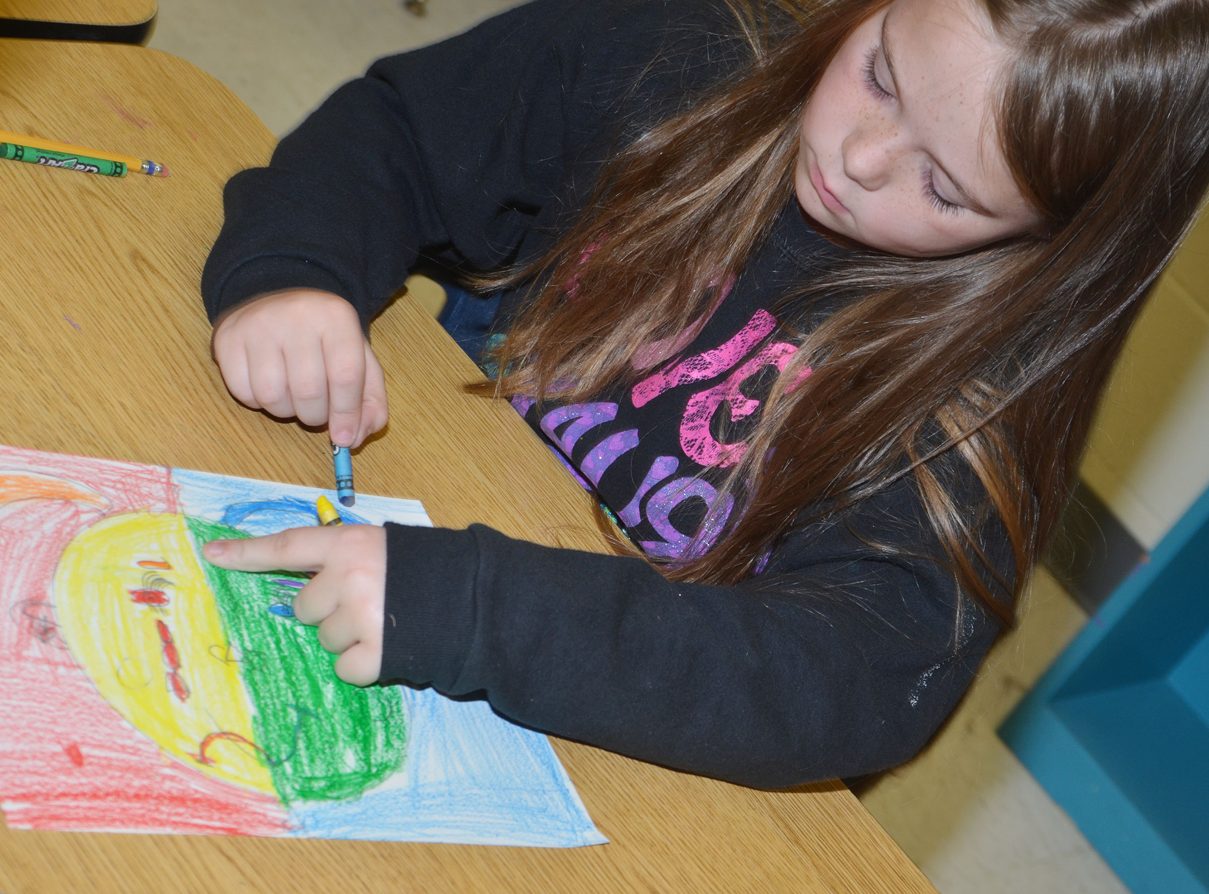 CES second-grader Cayleigh Underwood colors her warm and cool color face.