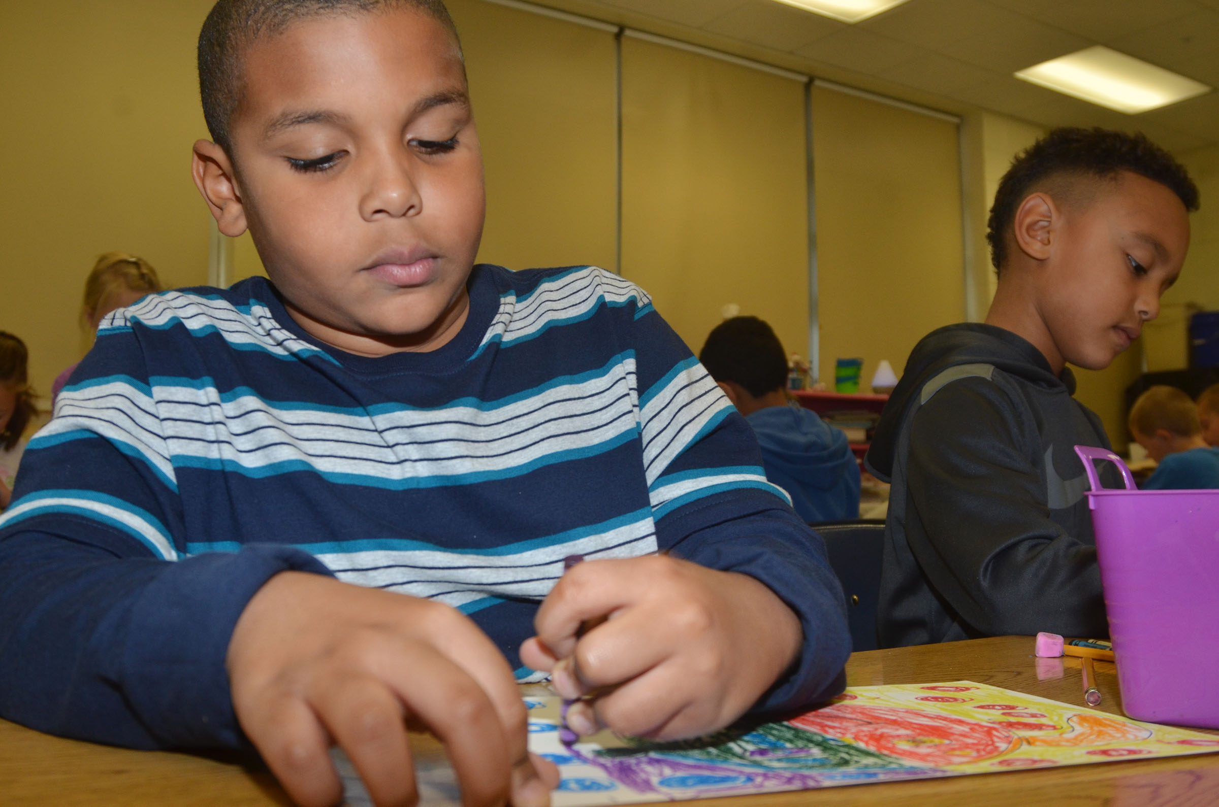 CES second-grader Zaemar Hoskins colors his warm and cool color face.