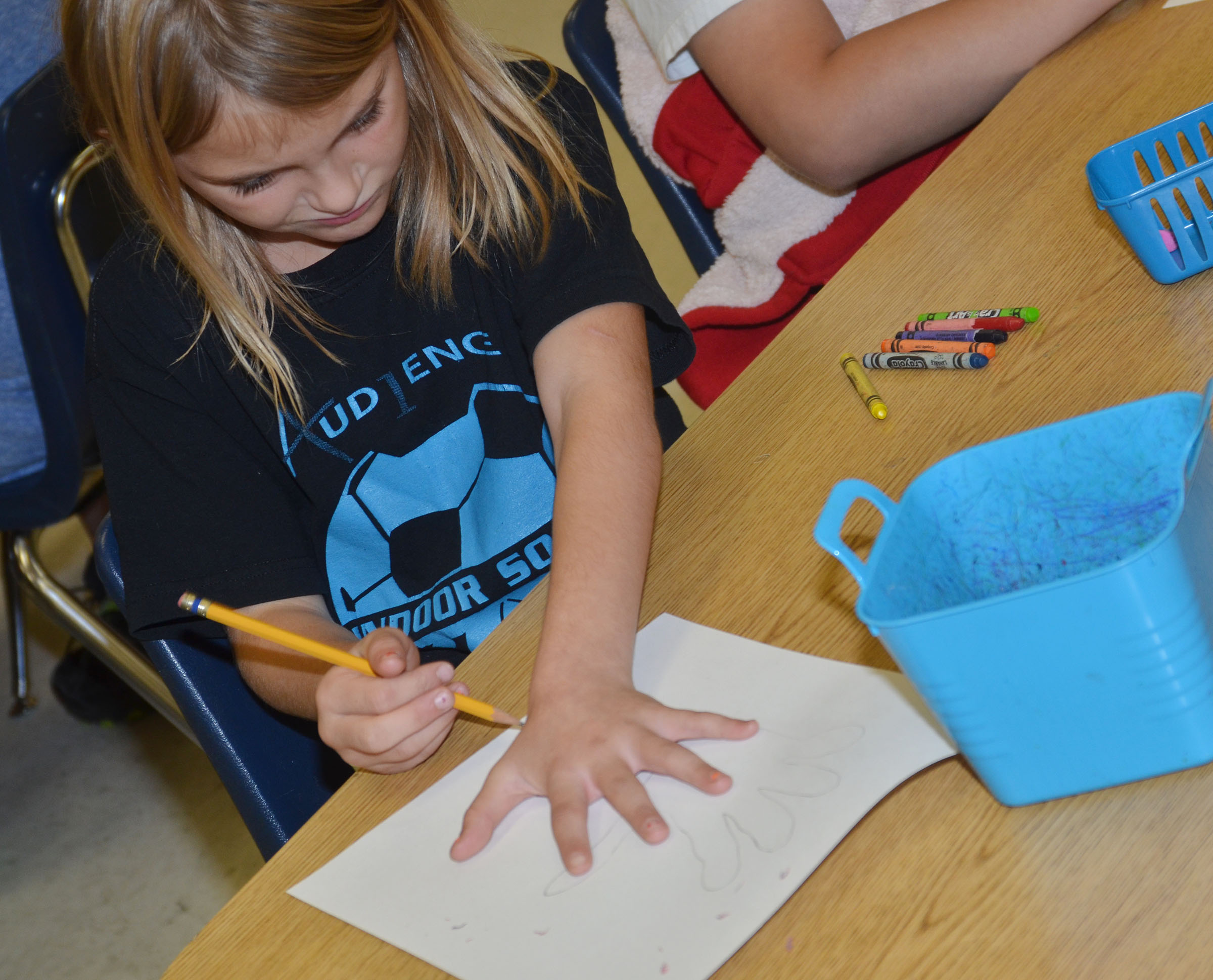 CES third-grader Miranda Edwards traces her hand.