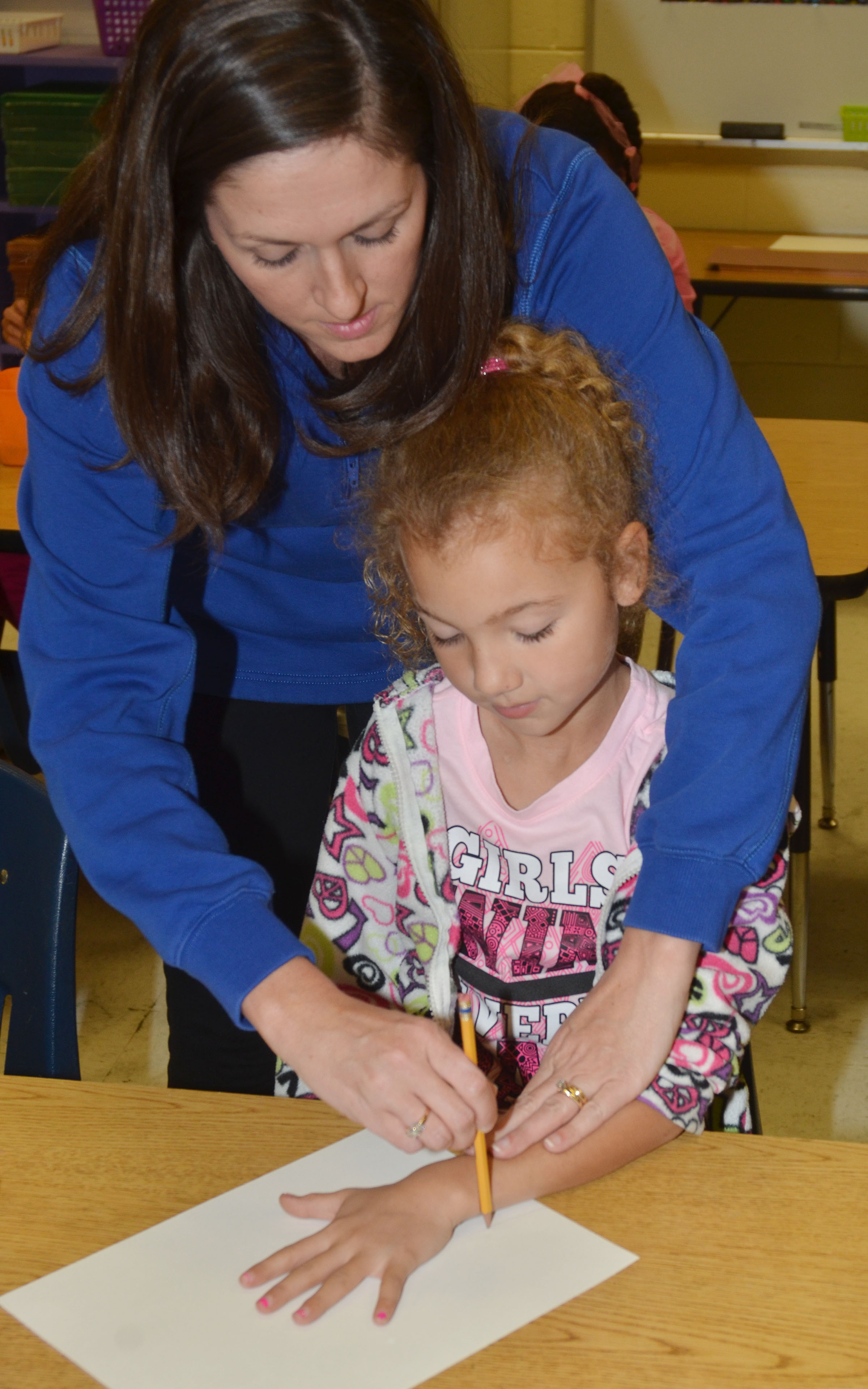 CES art teacher Adrienne Hash helps third-grader Raelyn Dunn trace her hand.