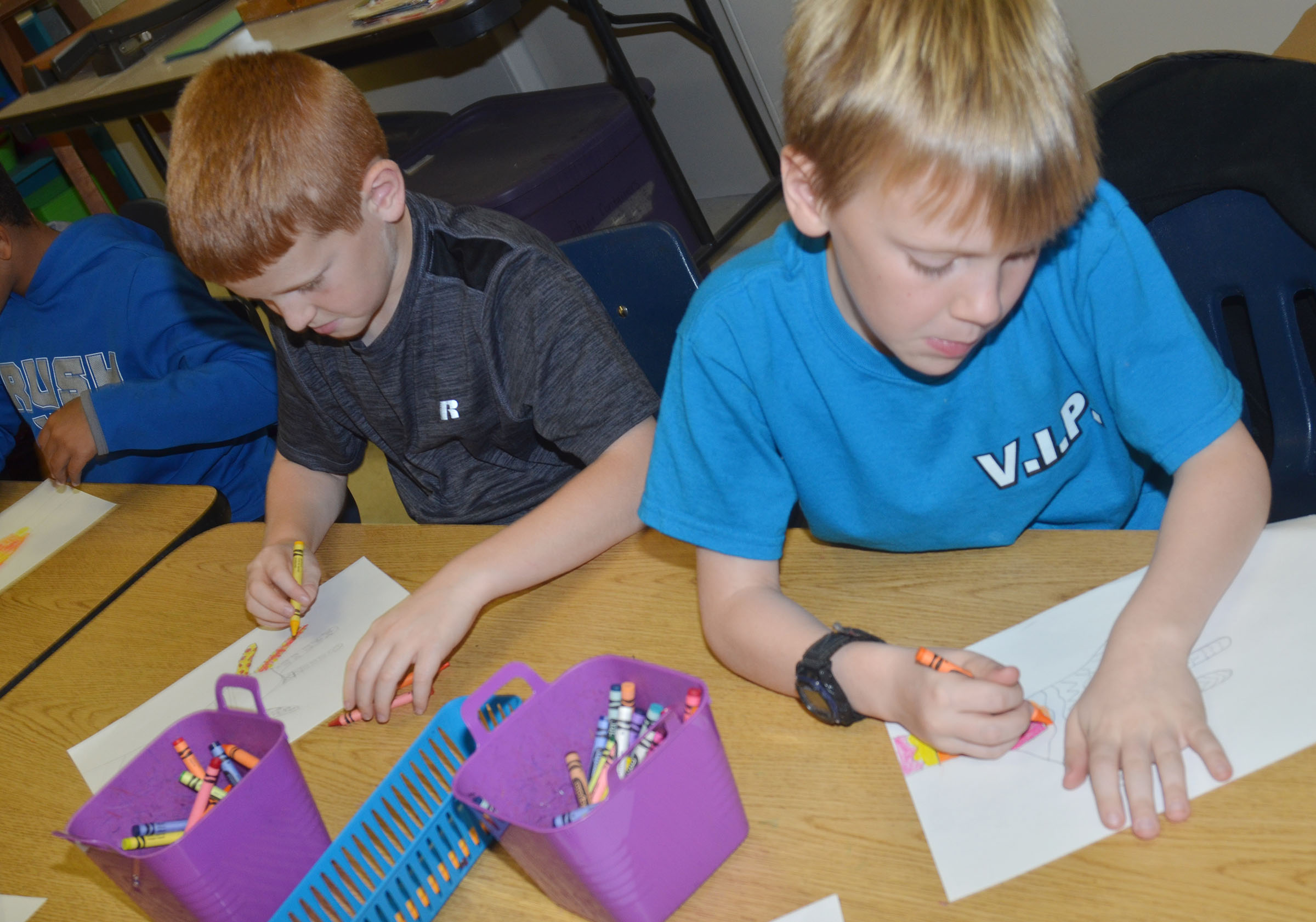 CES third-graders Westin Dudgeon, at left, and Timothy Coots color their hands with warm color designs.