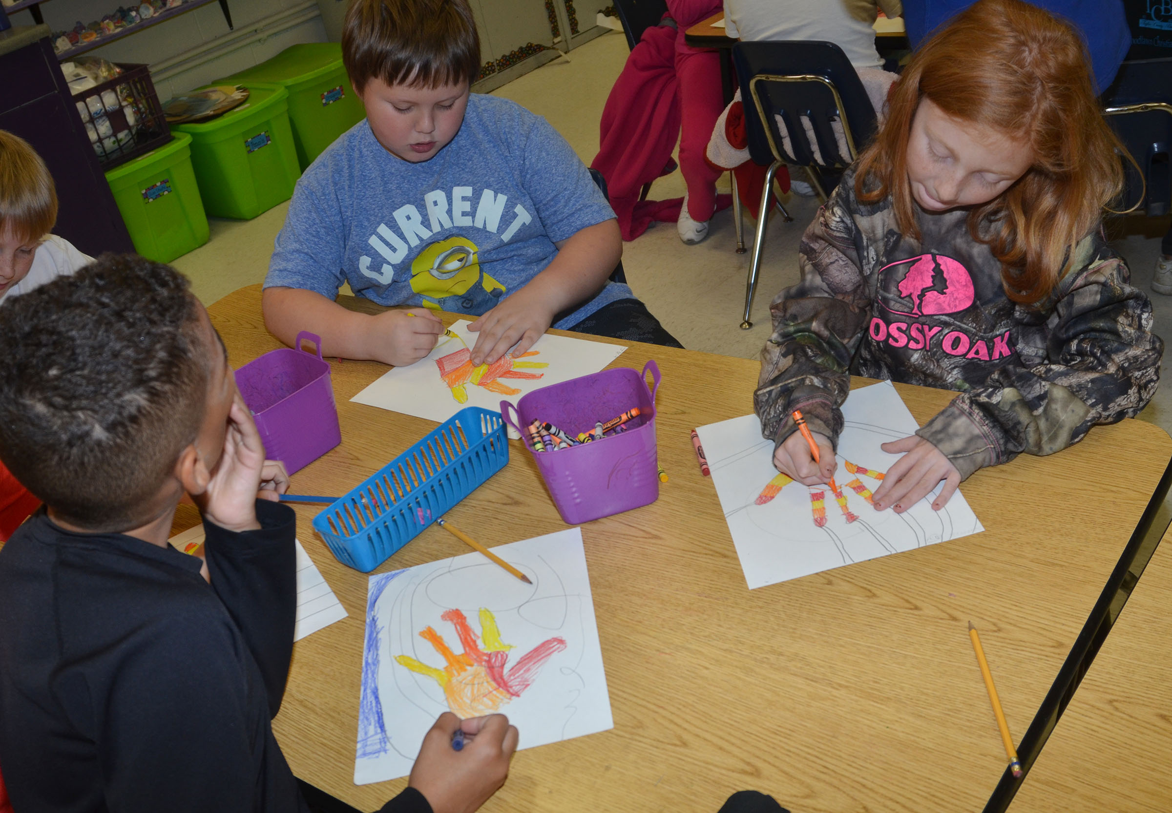 CES third-graders, from left, Jaden Barbee, Jace Cox and Savannah Wethington color their hands with warm color designs.