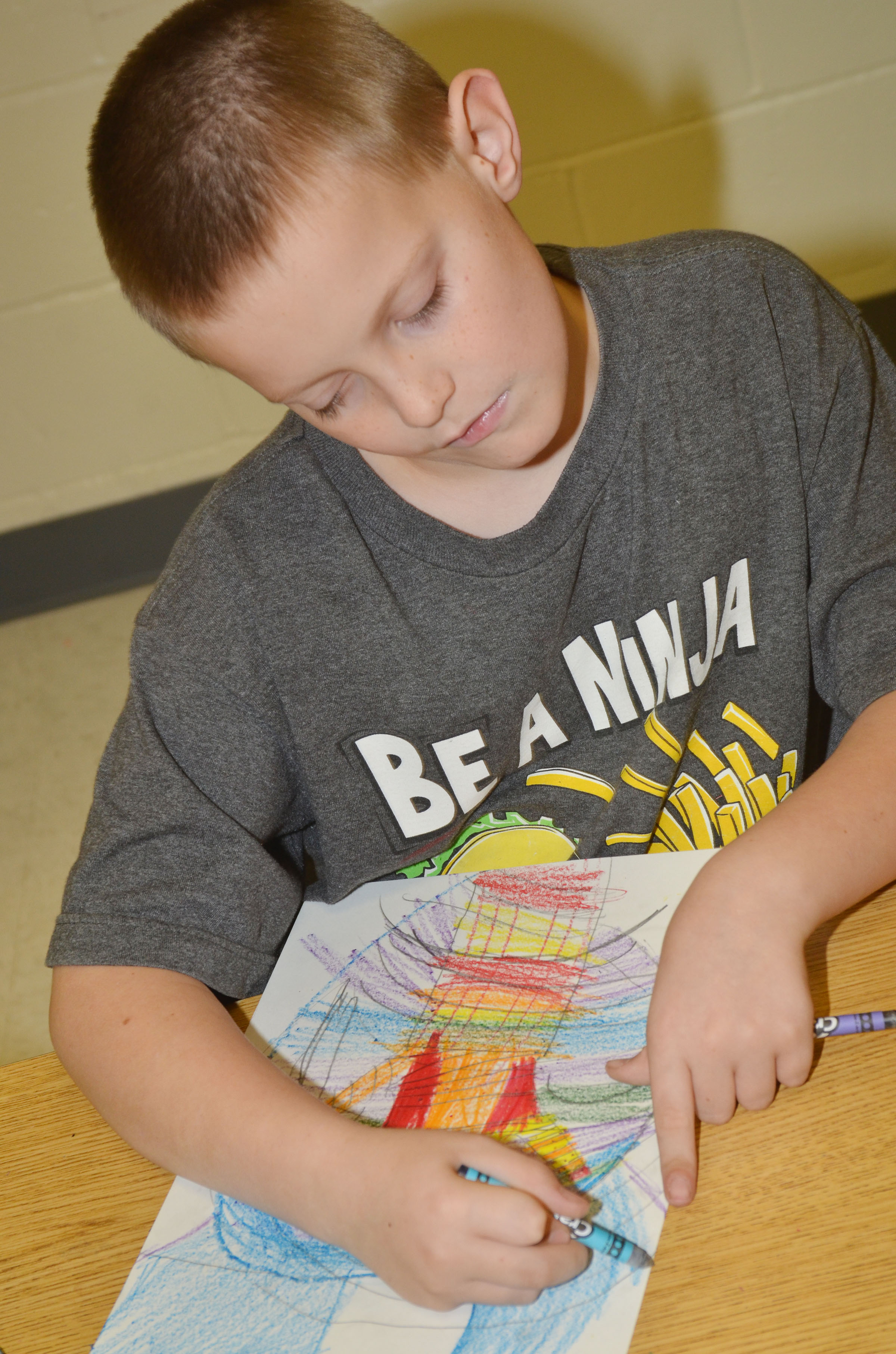 CES third-grader Bobby Engle colors his background with cool colors.