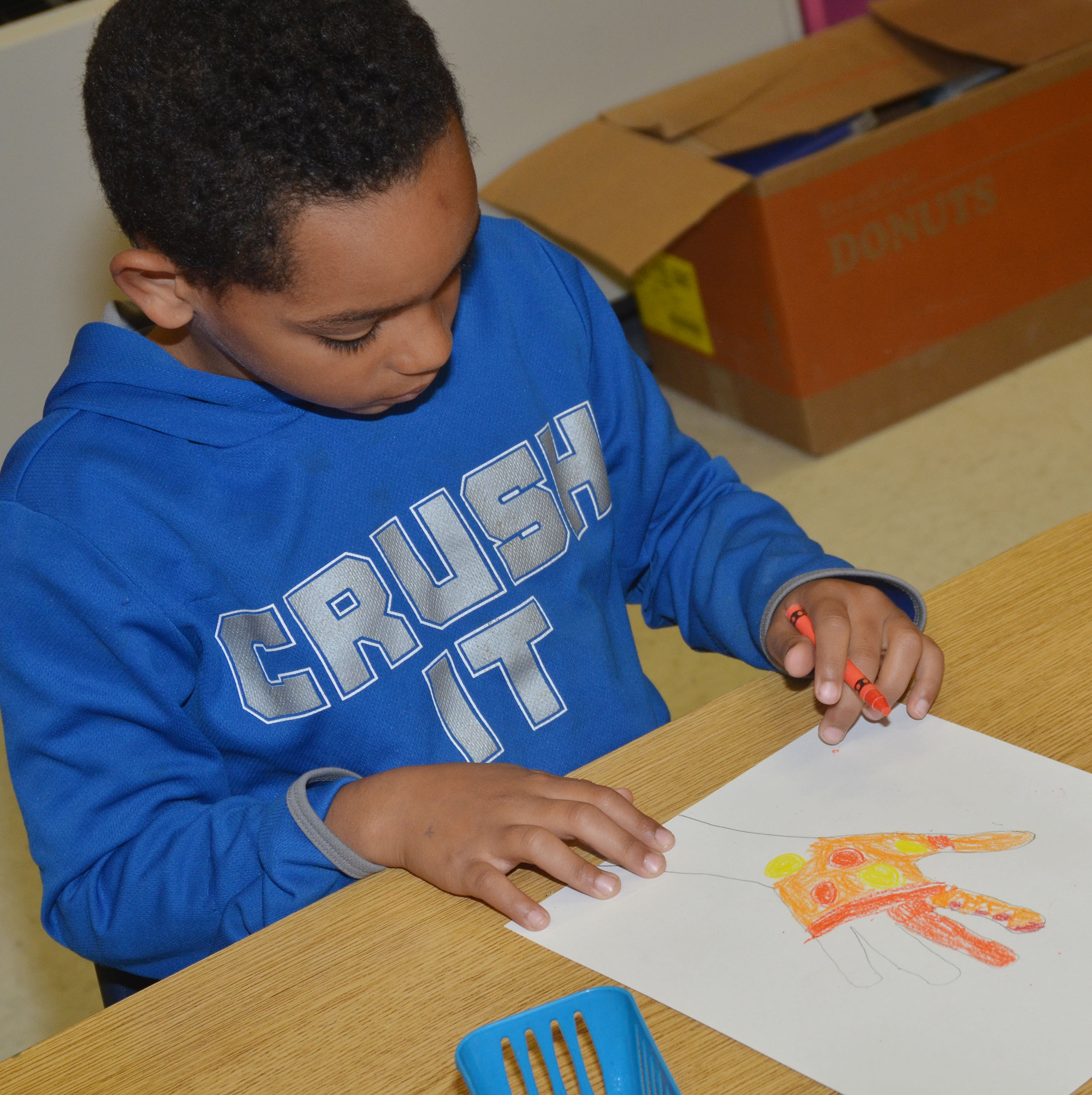 CES third-grader Jalen Embry colors his hand with warm color designs.