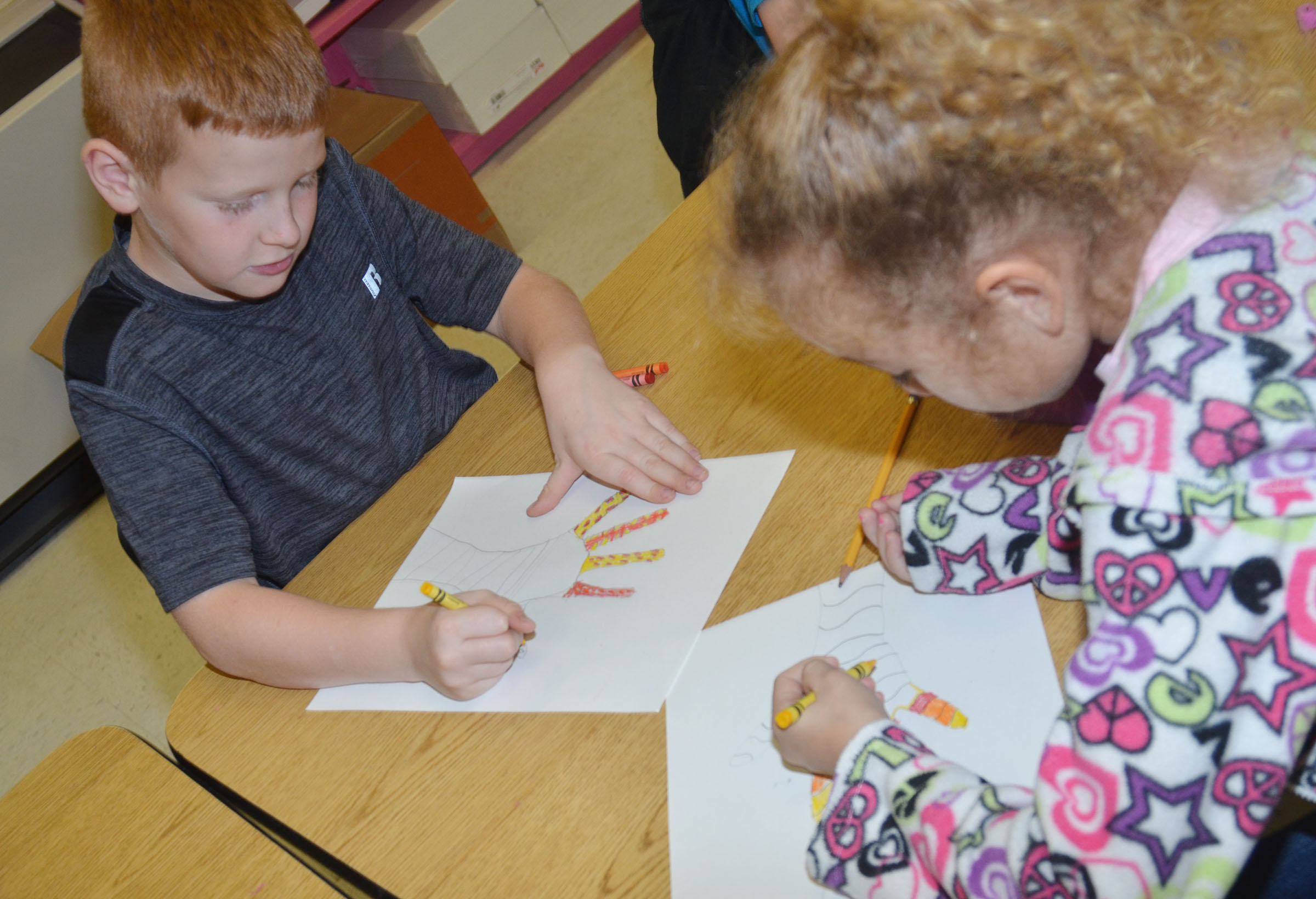 CES third-graders Westin Dudgeon, at left, and Raelyn Dunn color their hands with warm color designs.