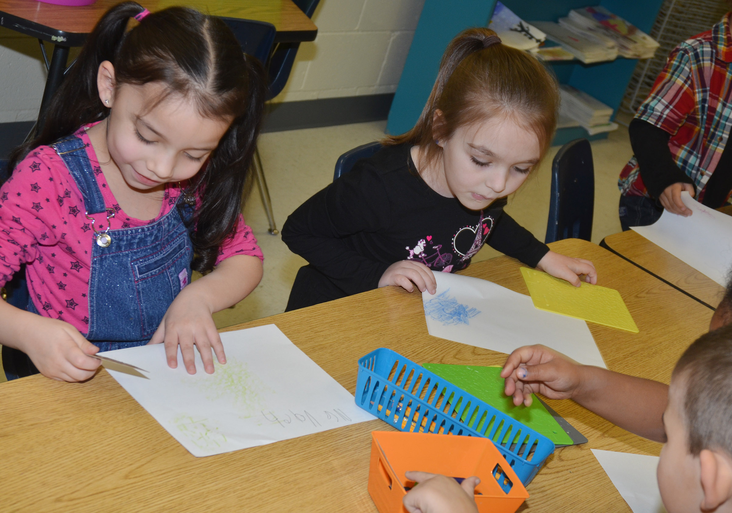 CES kindergarteners Nevaeh Agent, at left, and Aubrey Allen rub patterns.
