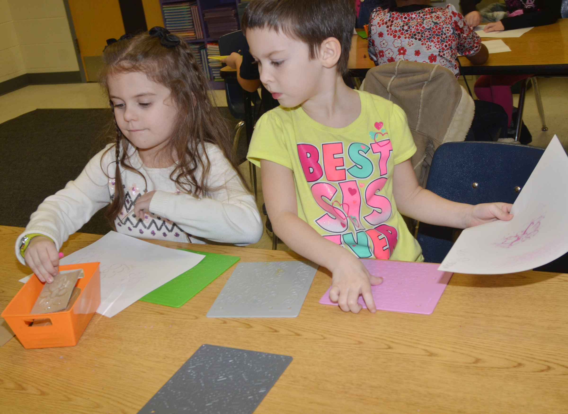 CES kindergarteners Addison Beckley, at left, and Madison Haywood rub patterns with crayons.