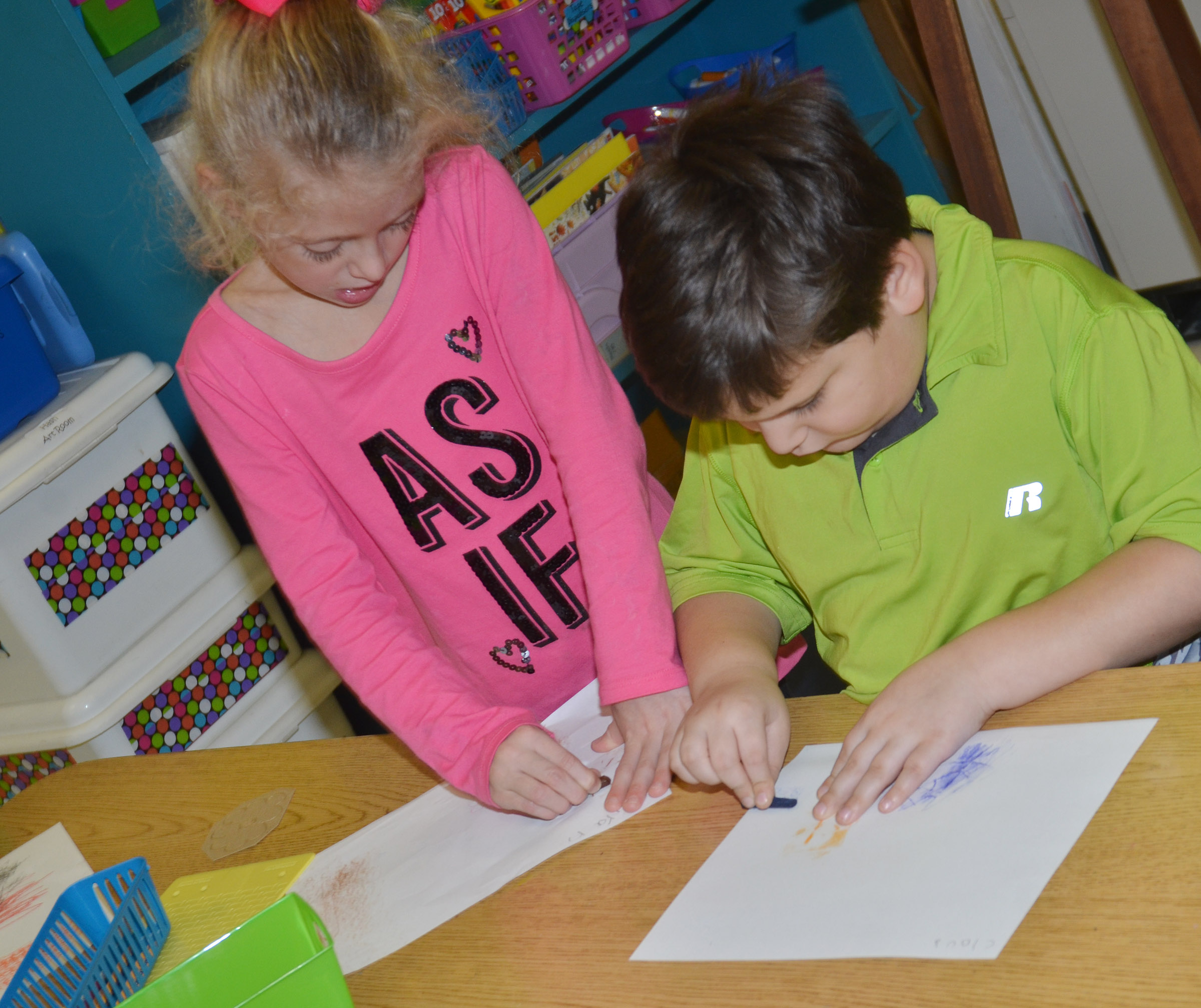 CES kindergarteners Aliyah Litsey, at left, and Cloud Malone rub patterns with crayons.