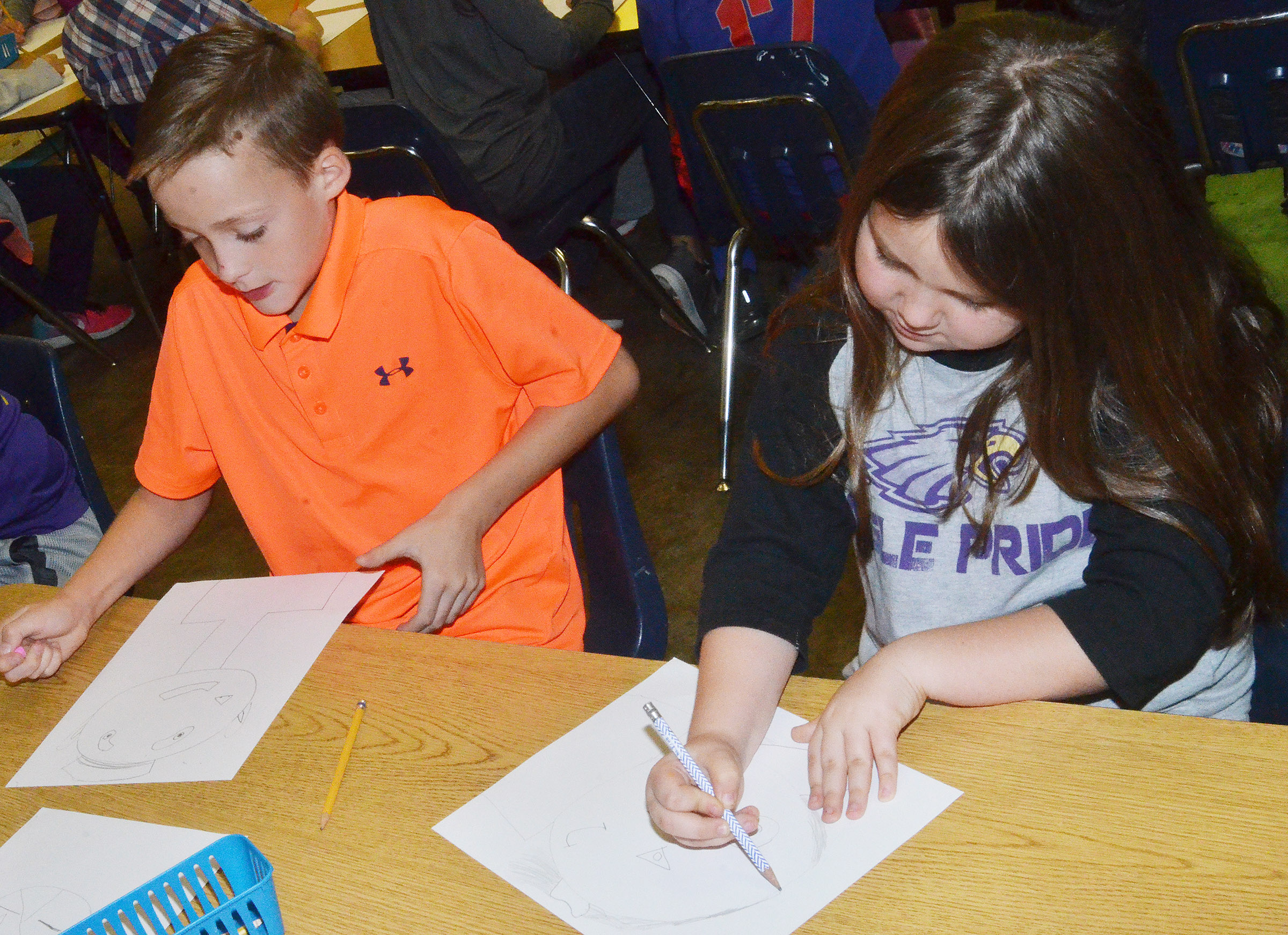CES fourth-graders Caysen Tungate, at left, and Maylee Wilds draw their distorted self-portraits.