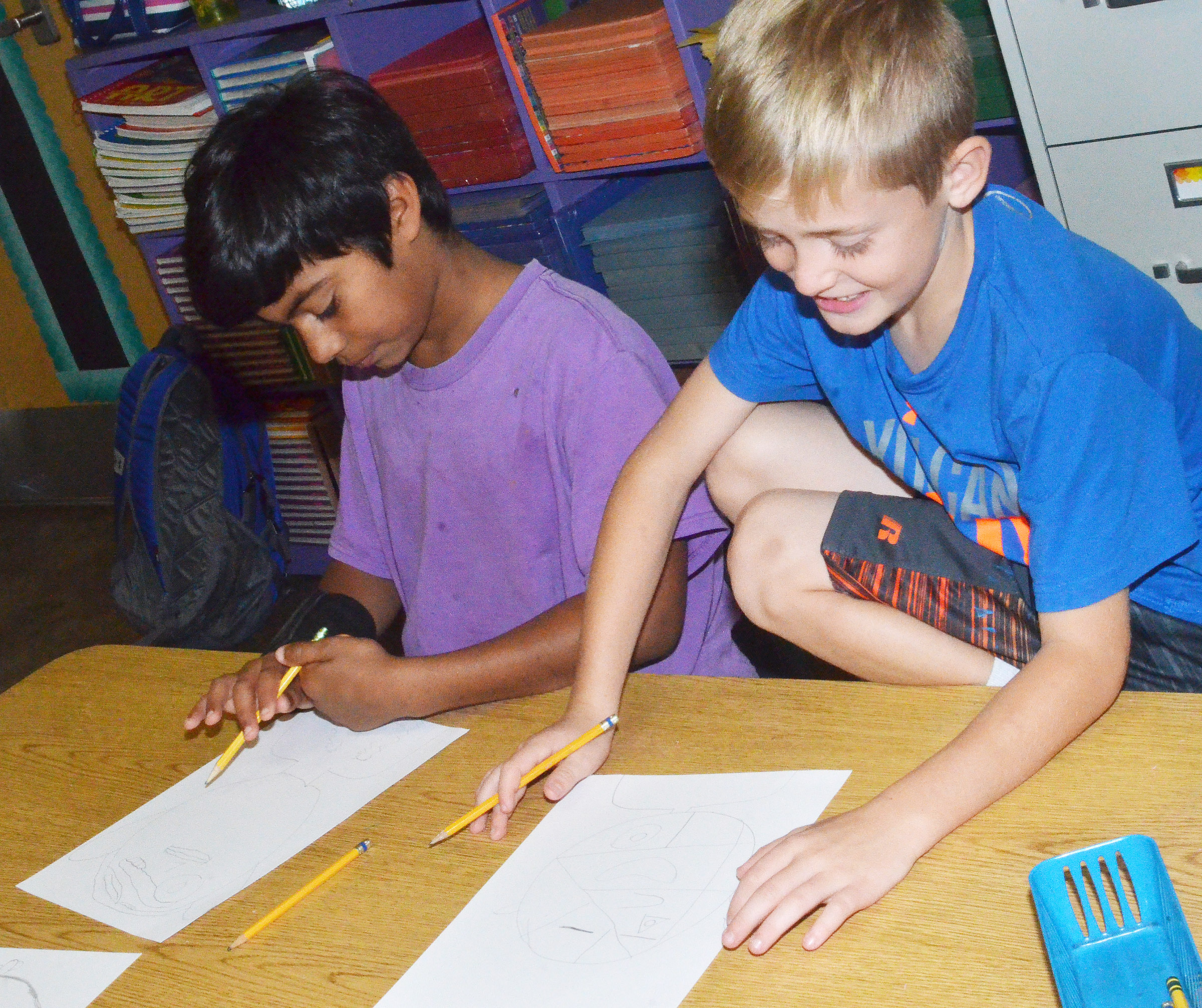 CES fourth-graders LaDainien Smith, at left, and Braydn Spurling draw their distorted self-portraits.