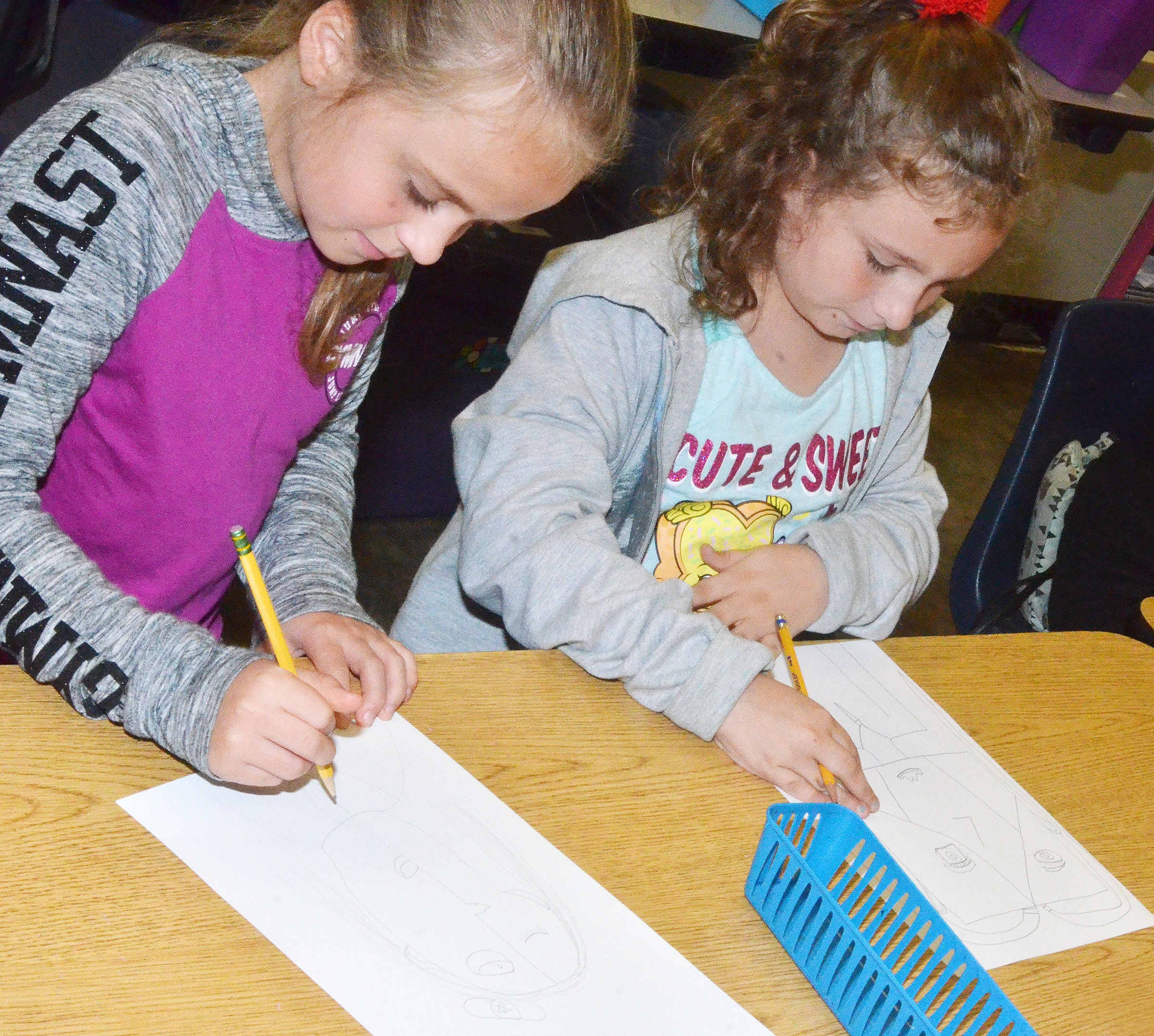 CES fourth-graders Kennedy Griffiths, at left, and Aliyah Burton draw their distorted self-portraits.