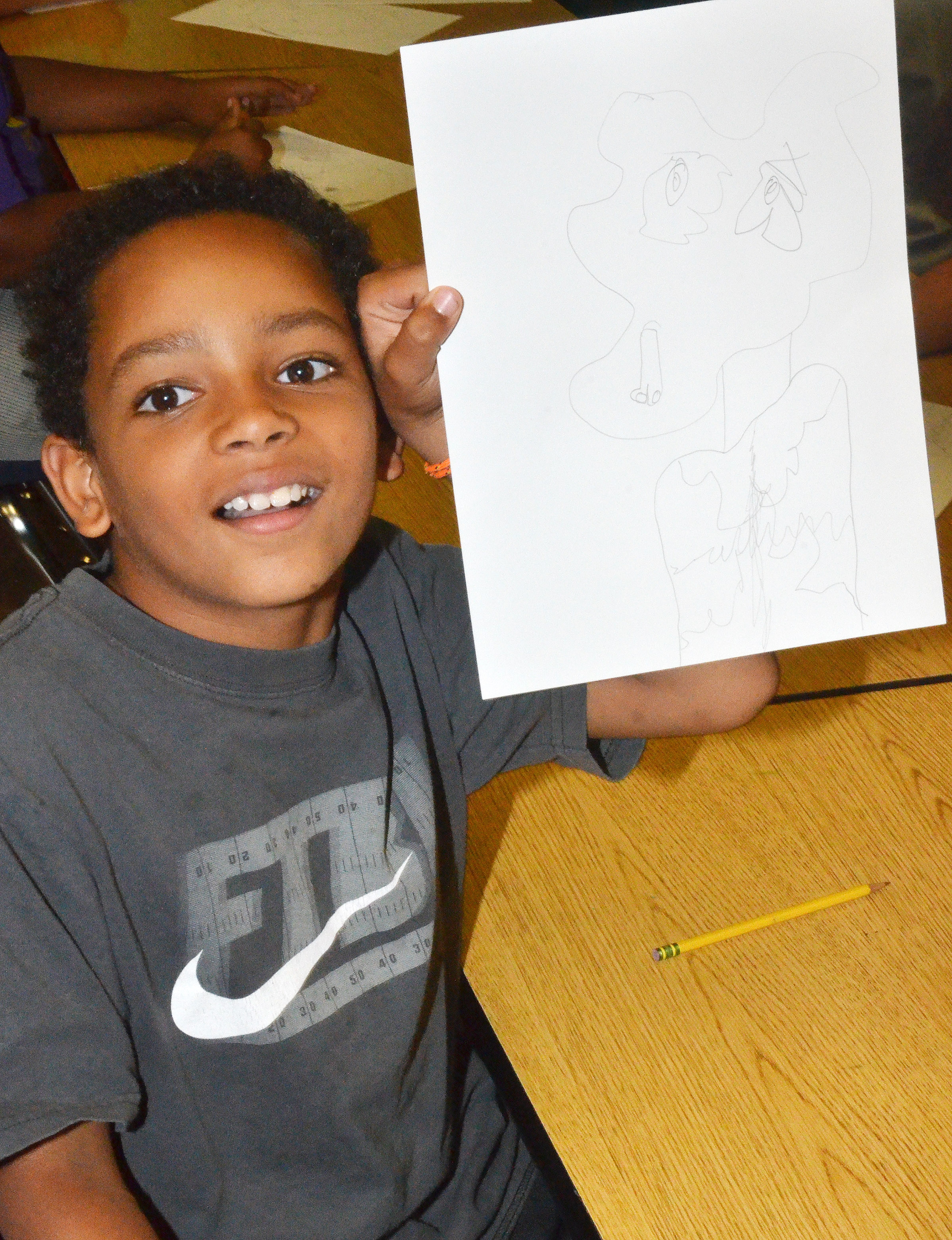 CES fourth-grader Jalen Embry holds his finished distorted self-portrait.