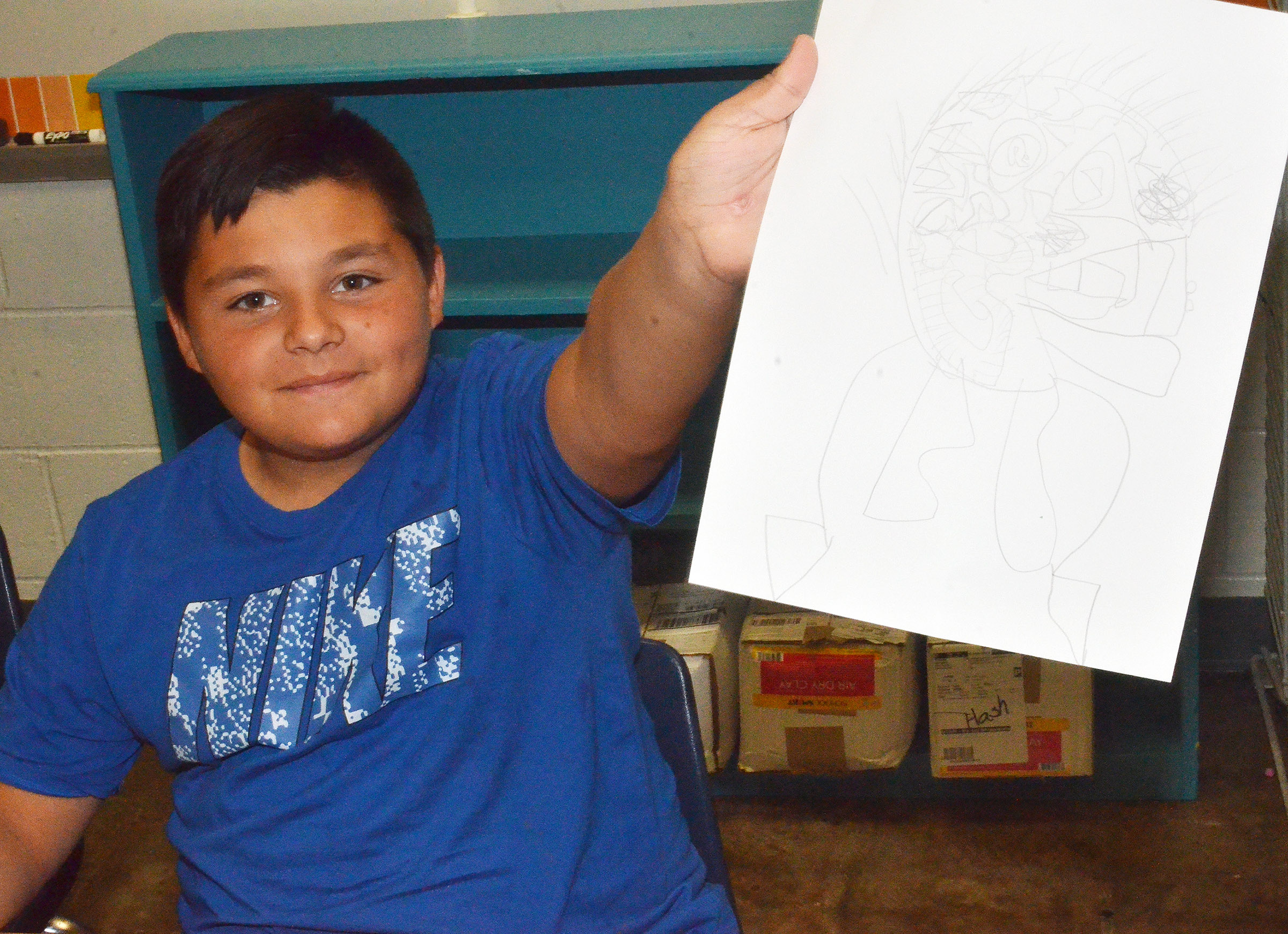 CES fourth-grader Brayden Paiz holds his finished distorted self-portrait.