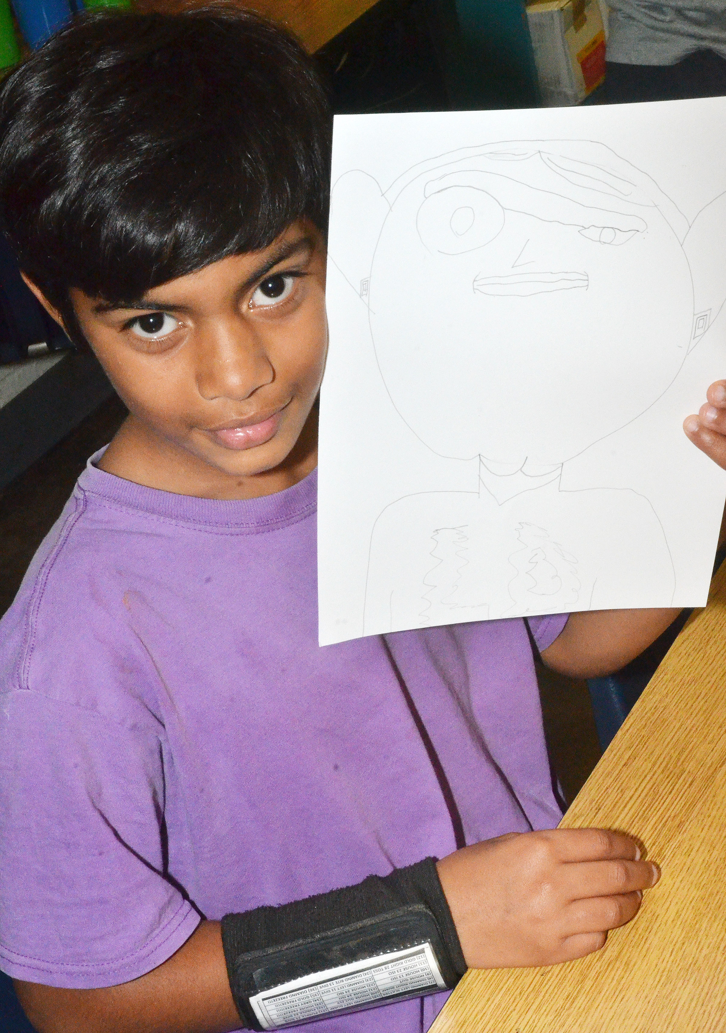 CES fourth-grader LaDainien Smith holds his finished distorted self-portrait.