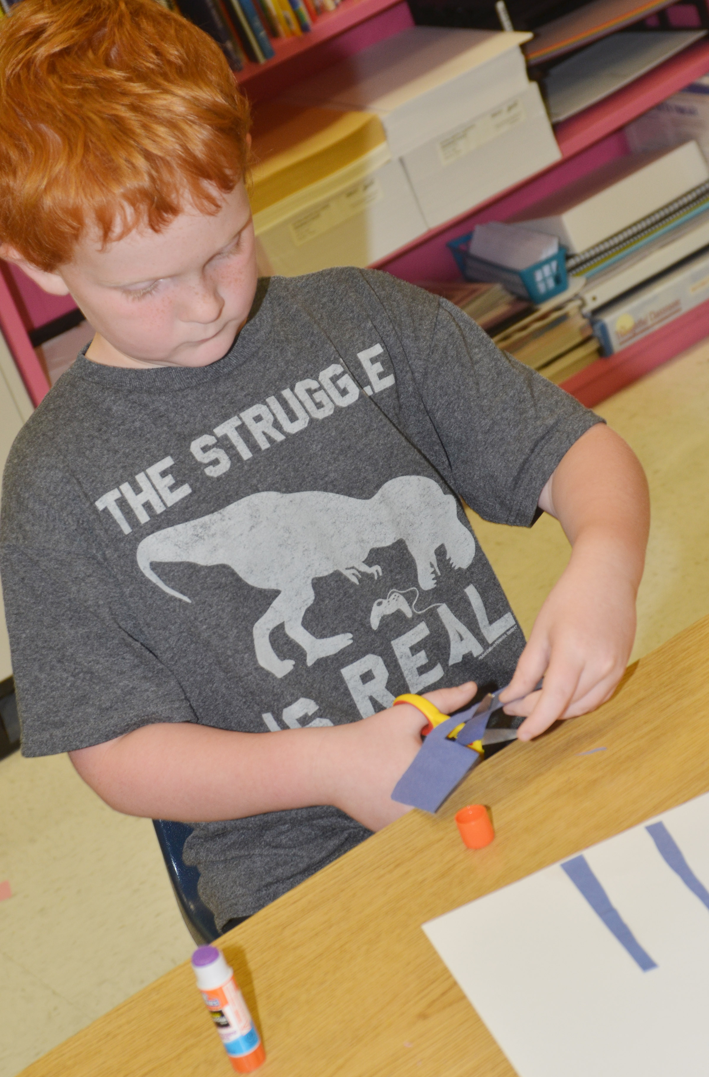 CES third-grader Gavin Martin cuts out construction paper as he creates his drawing.