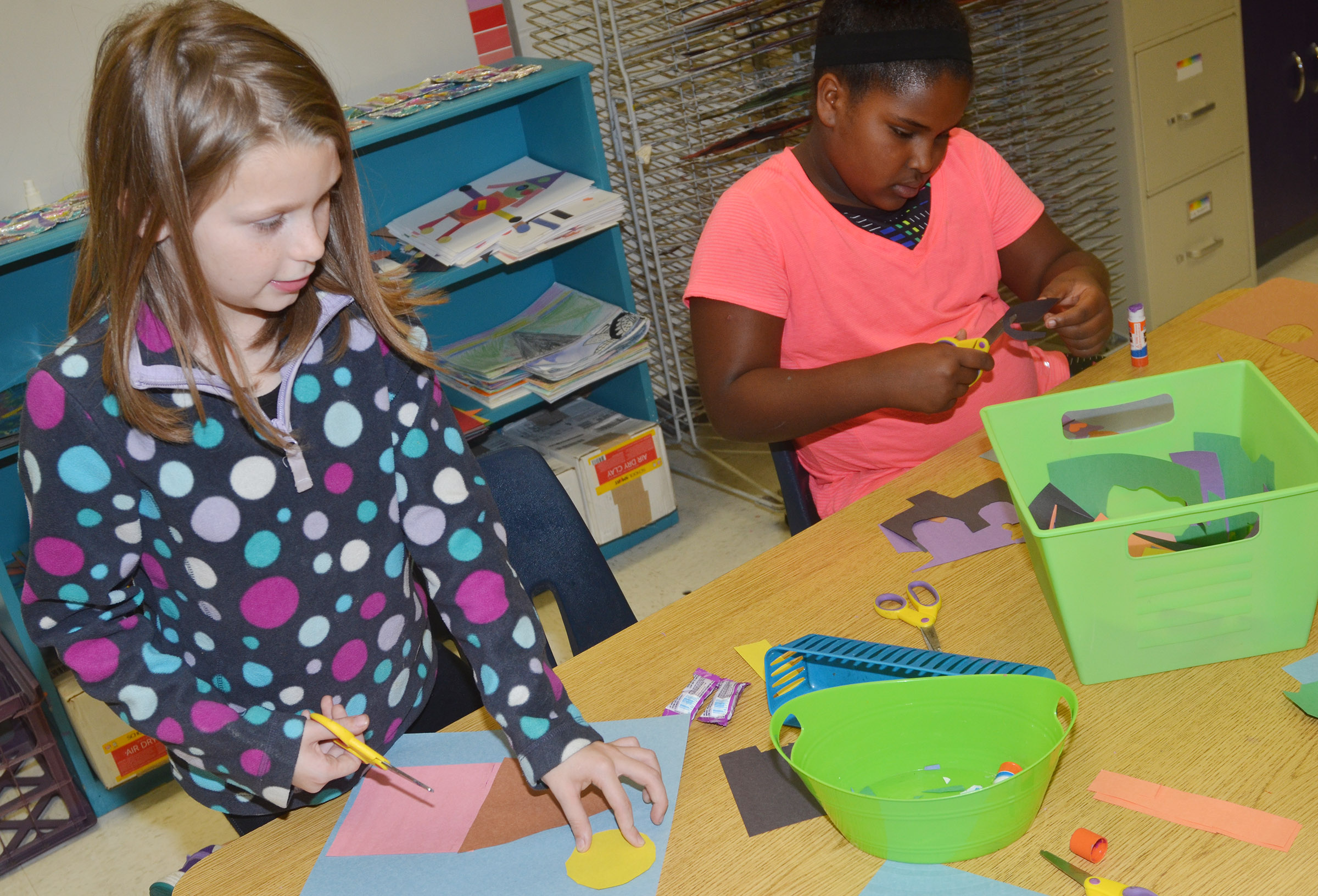 CES third-graders Sammantha Wooley, at left, and Ajada Smith cut out construction paper as they create their drawings.