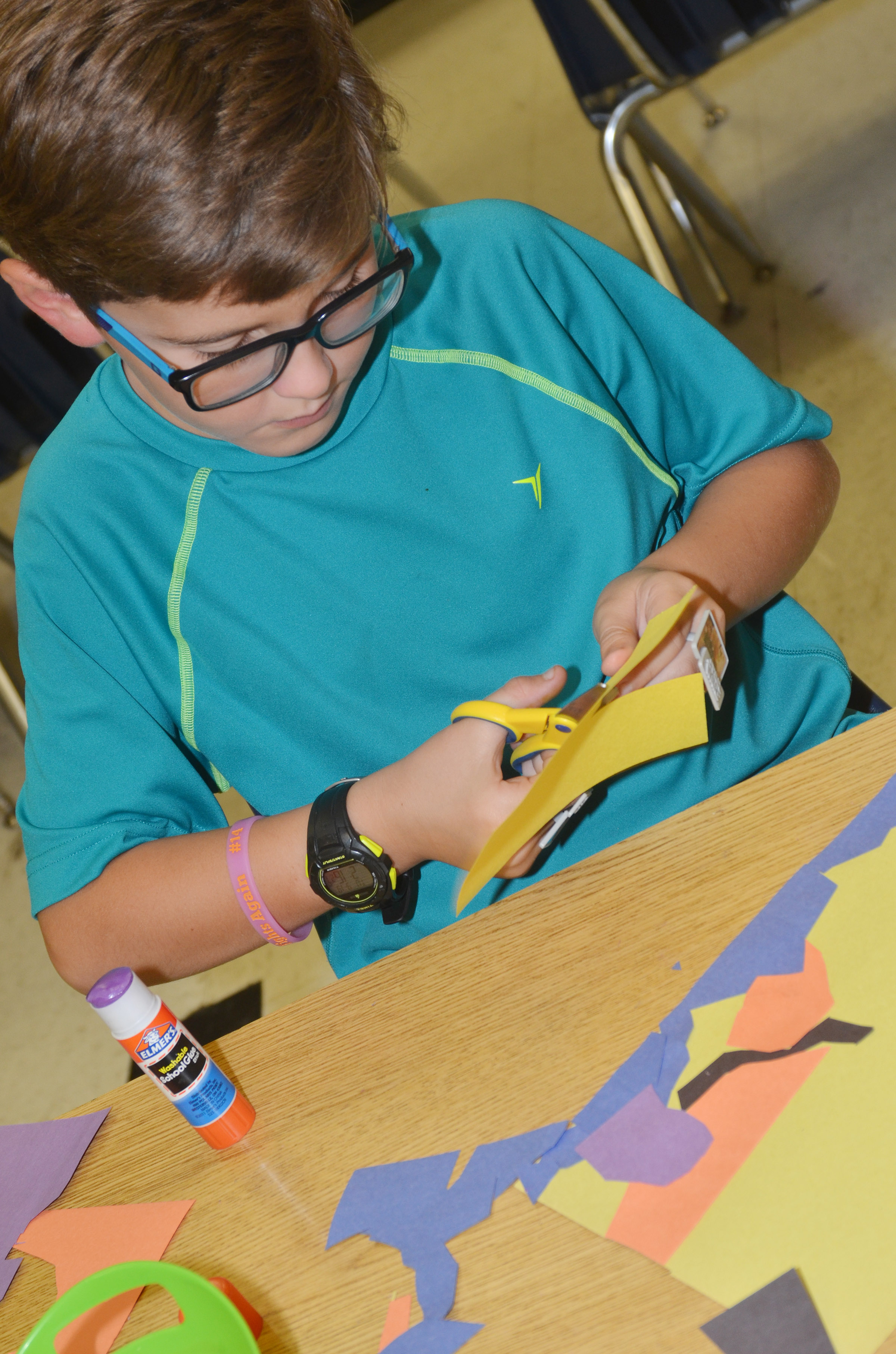 CES third-grader Tye Rhodes cuts out construction paper as he creates his drawing.