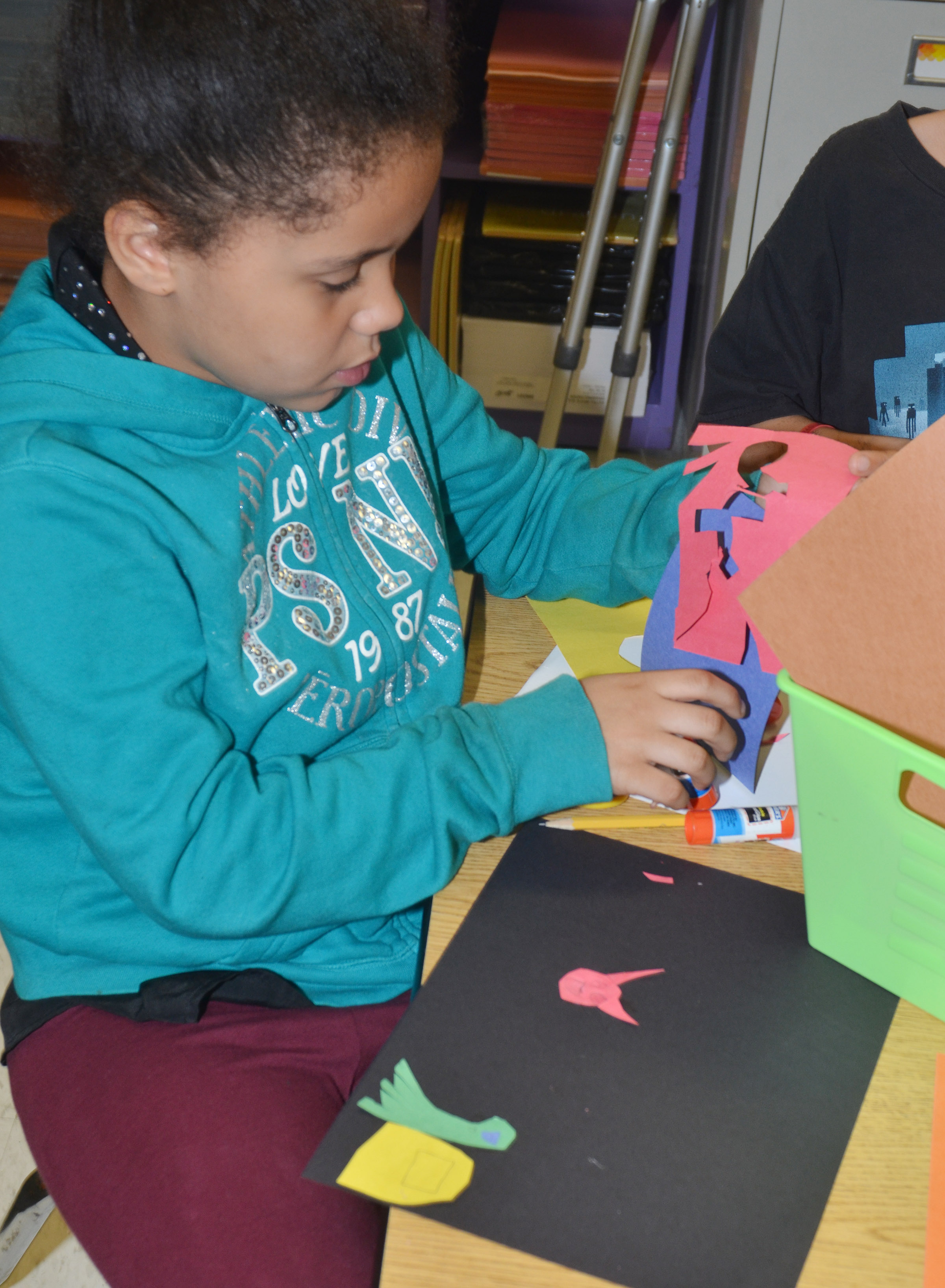 CES third-grader Alex Wilson cuts out construction paper as she creates her drawing.