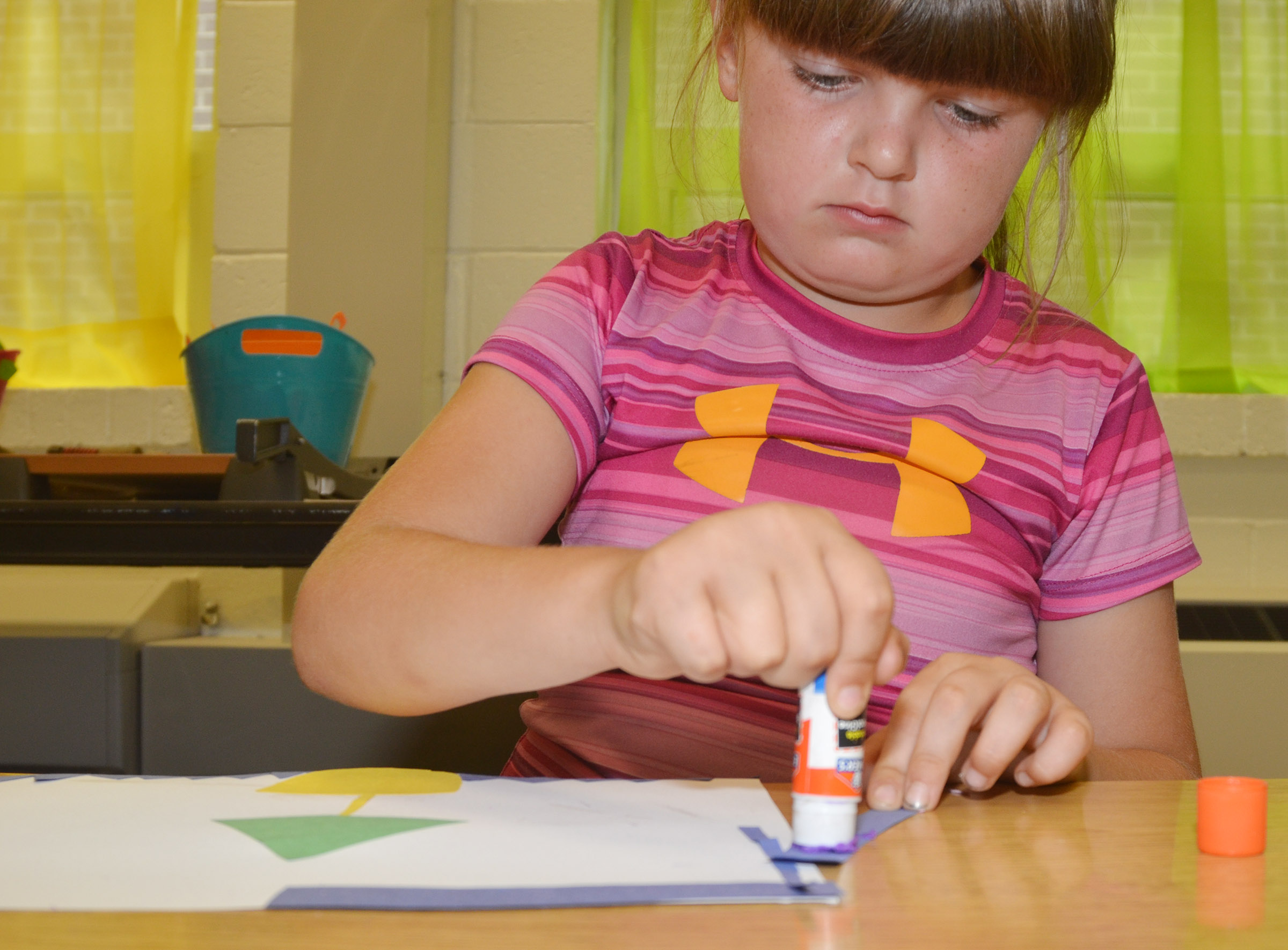 CES third-grader Kaleigh Wilhoite glues shapes on her construction paper as she creates her drawing.