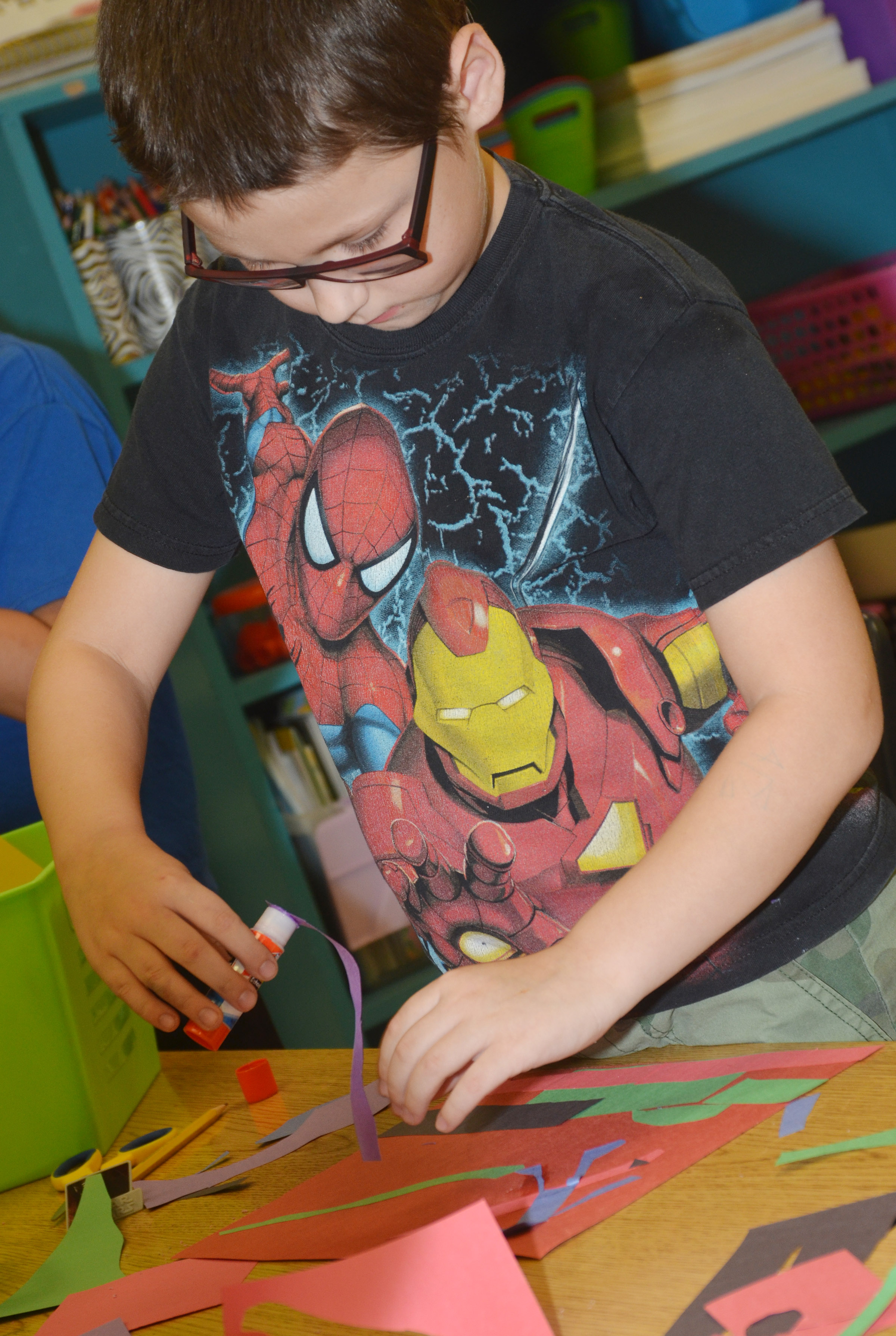 CES third-grader Cobain Carter glues shapes on his construction paper as he creates his drawing.