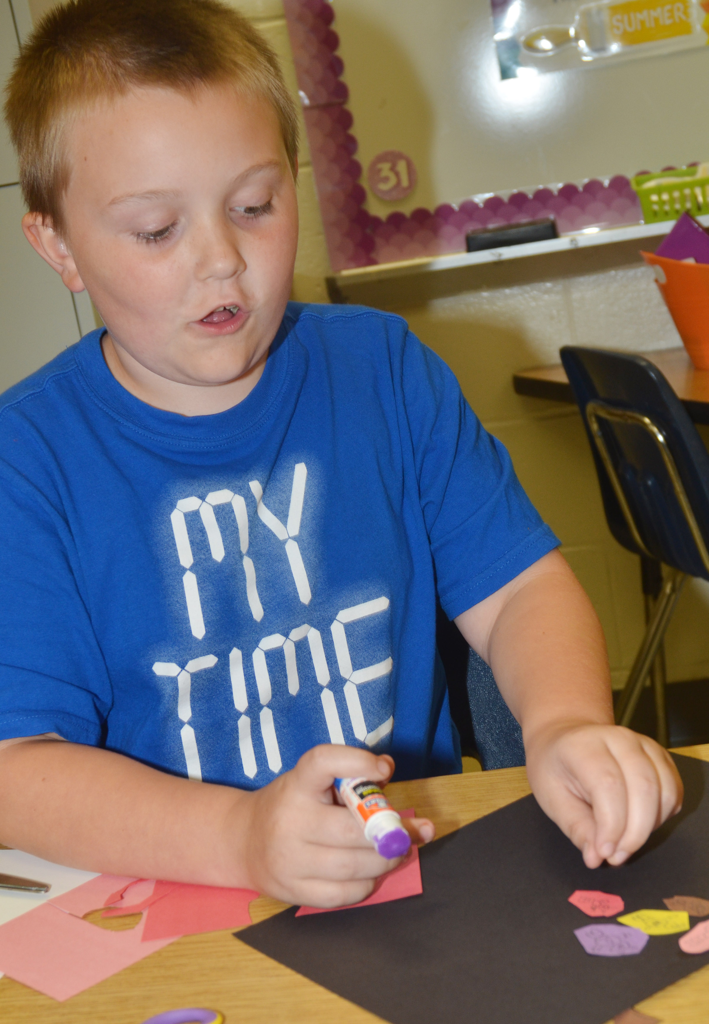 CES third-grader Griffin Skaggs cuts out construction paper as he creates his drawing.