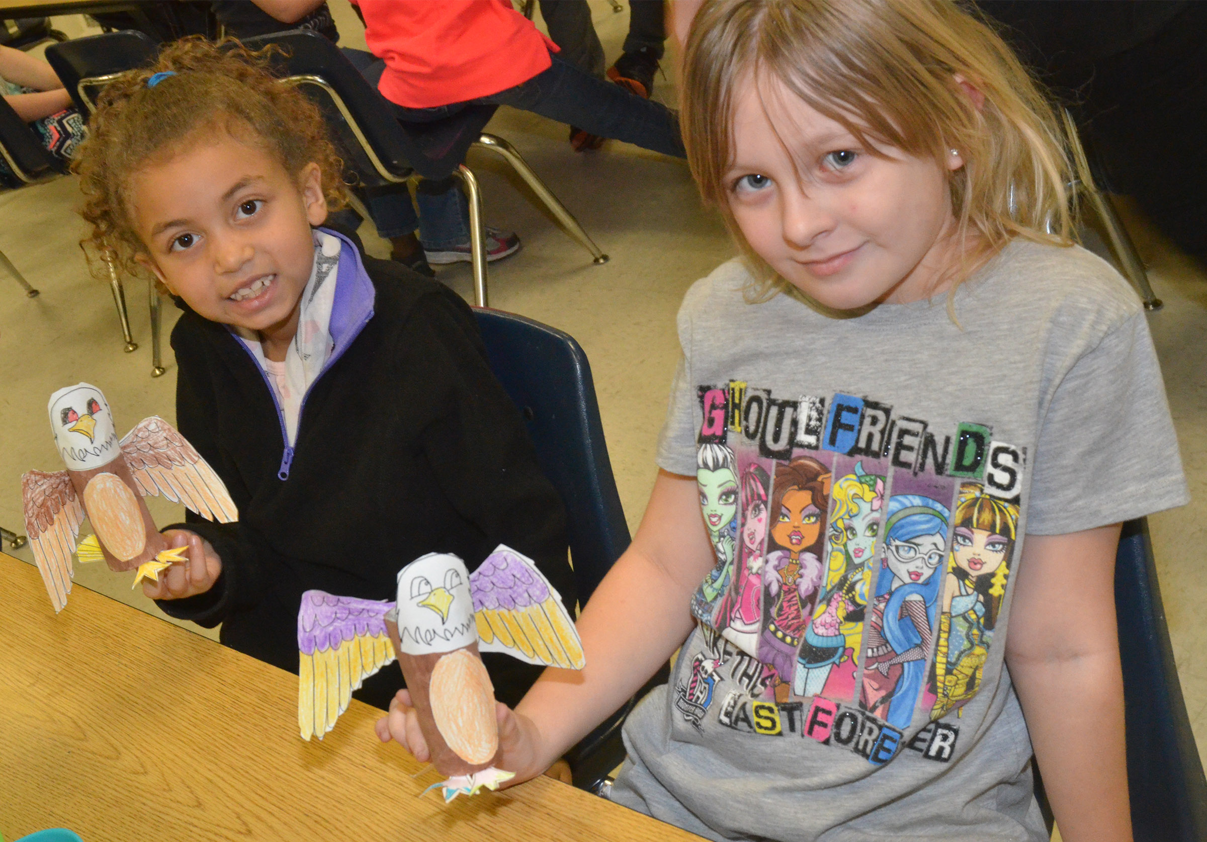 CES first-graders Londyn Smith, at left, and Allison Dean hold their finished Eagles.