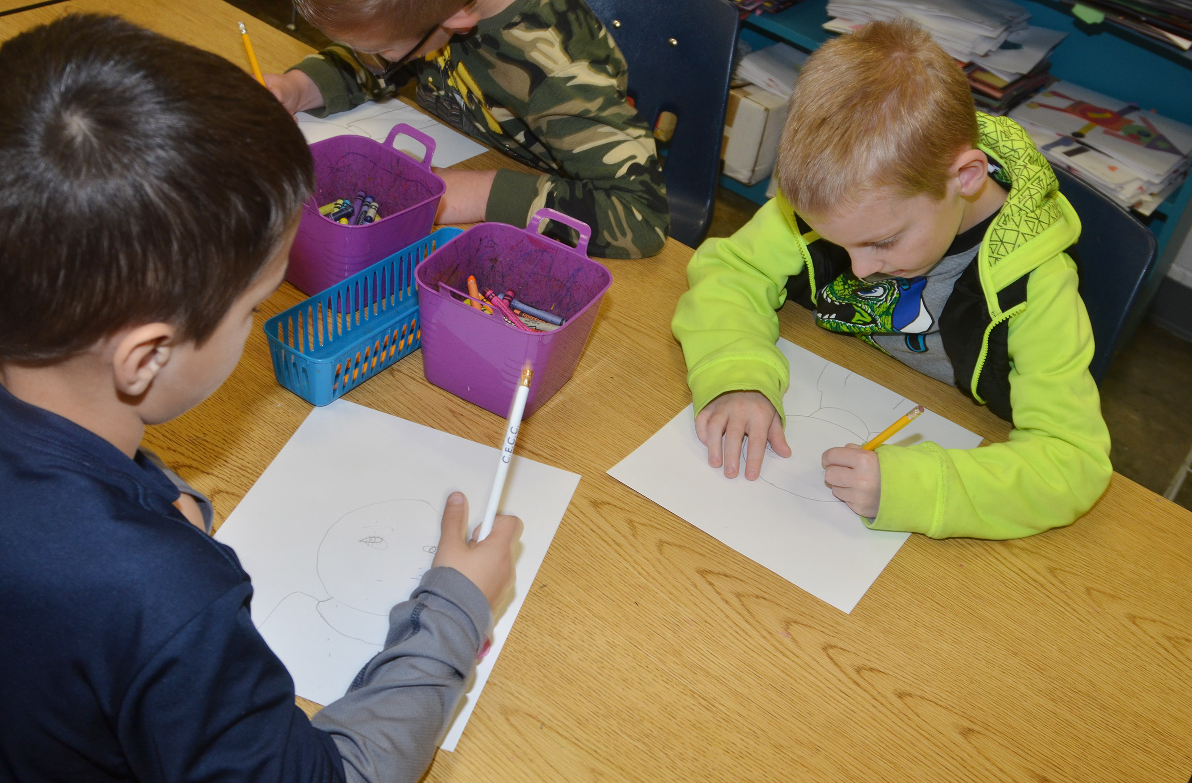 CES second-graders Brenden Chastain, at left, and Brandon Thompson draw their self-portraits.