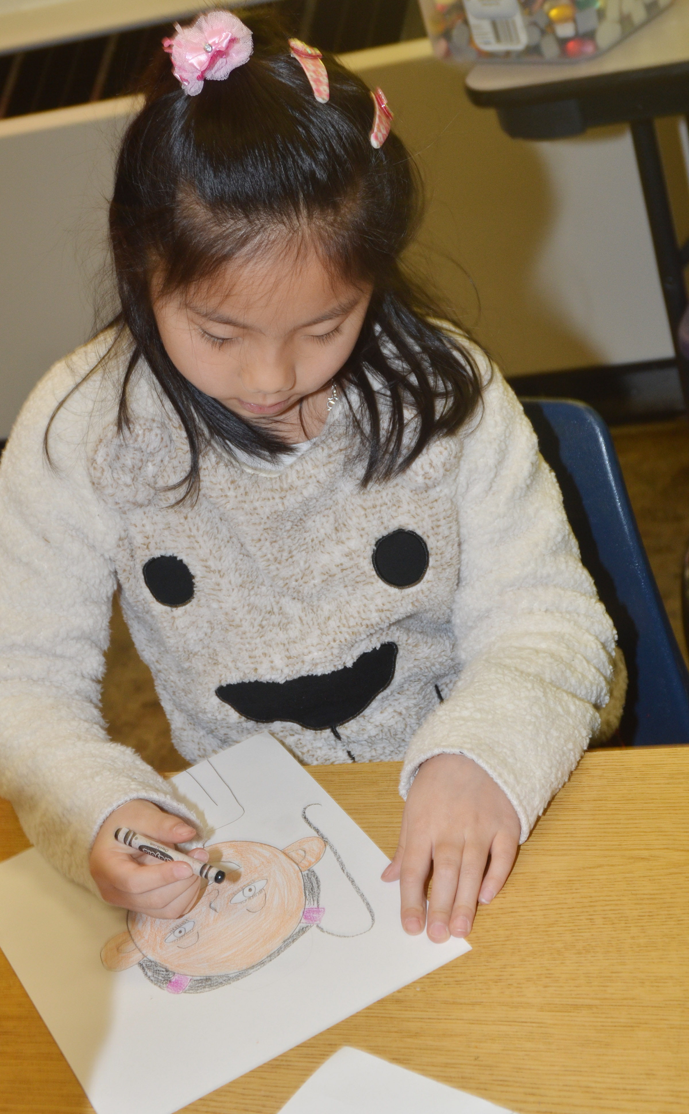 CES second-grader Tina Jiang colors her self-portrait.