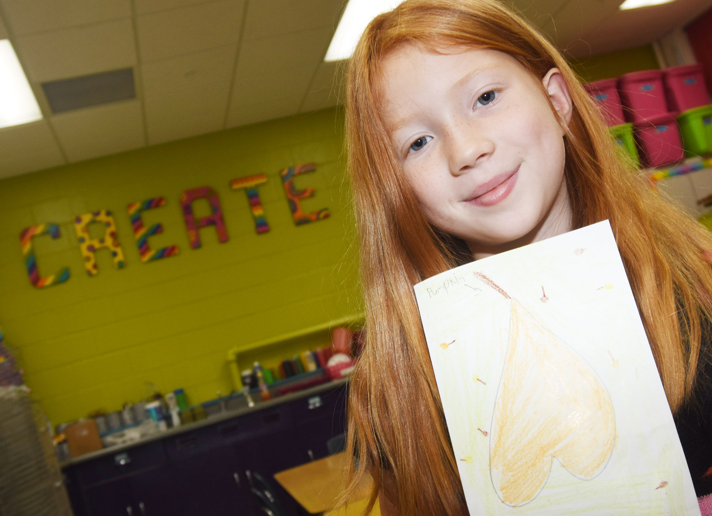 CES first-grader Bella Stout holds her fall scene.
